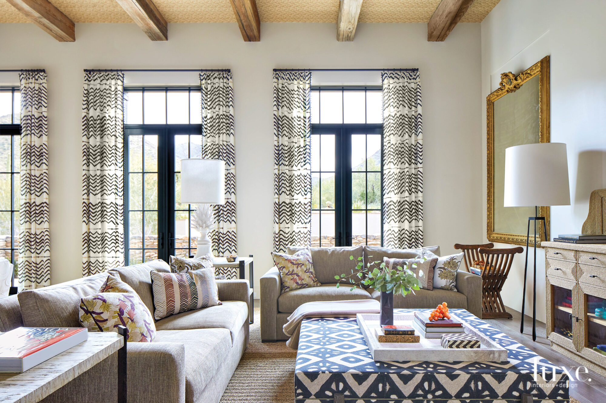 Patterned curtains frame the living...