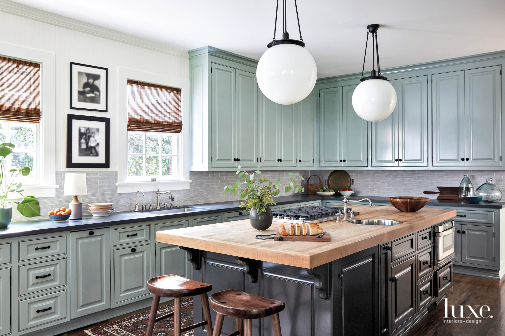Kitchen with pale green painted cabinets and a wood counter island with black cabinets.