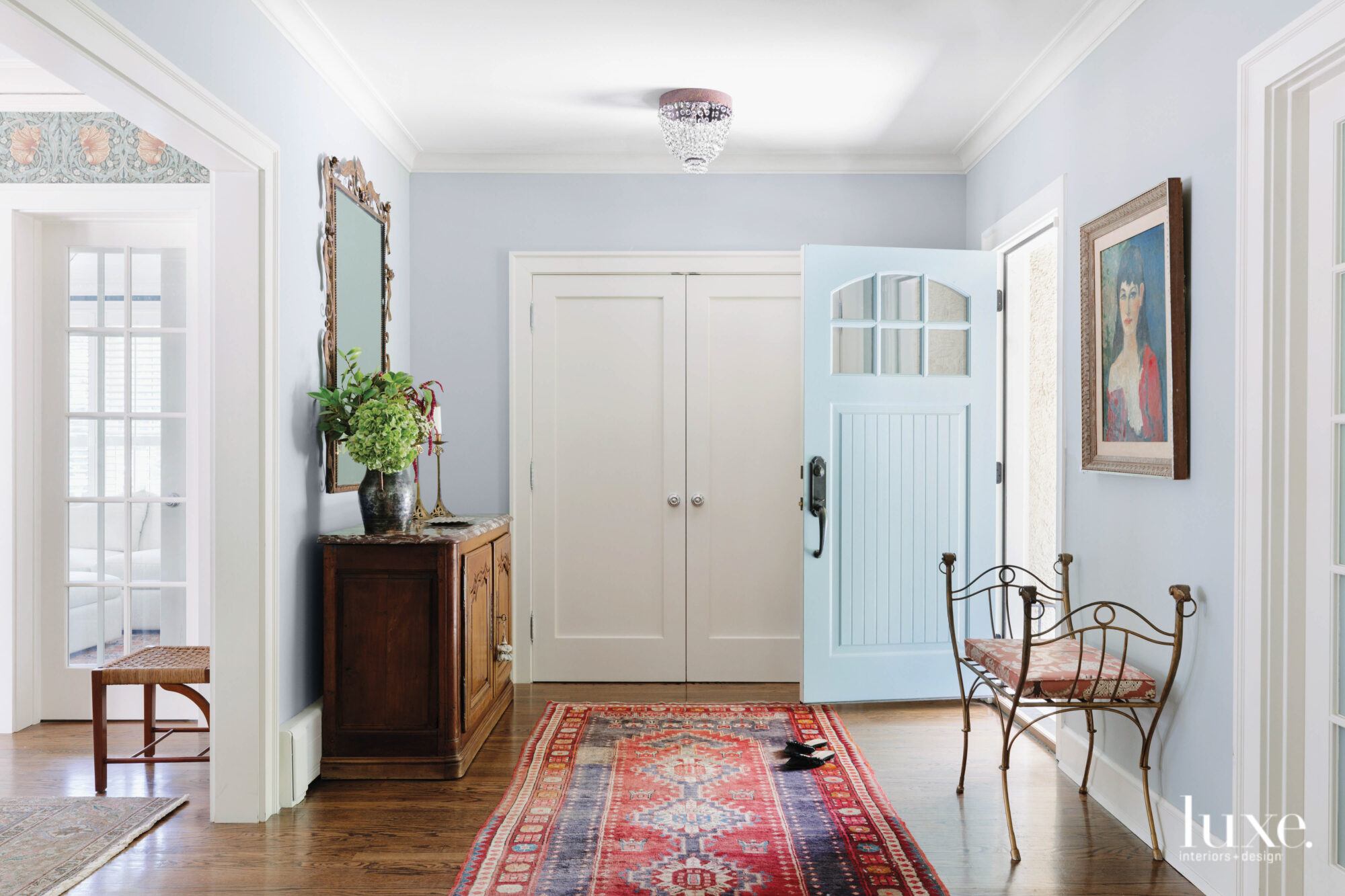 A colorful runner and a blue farmhouse door welcome visitors into the home's entryway