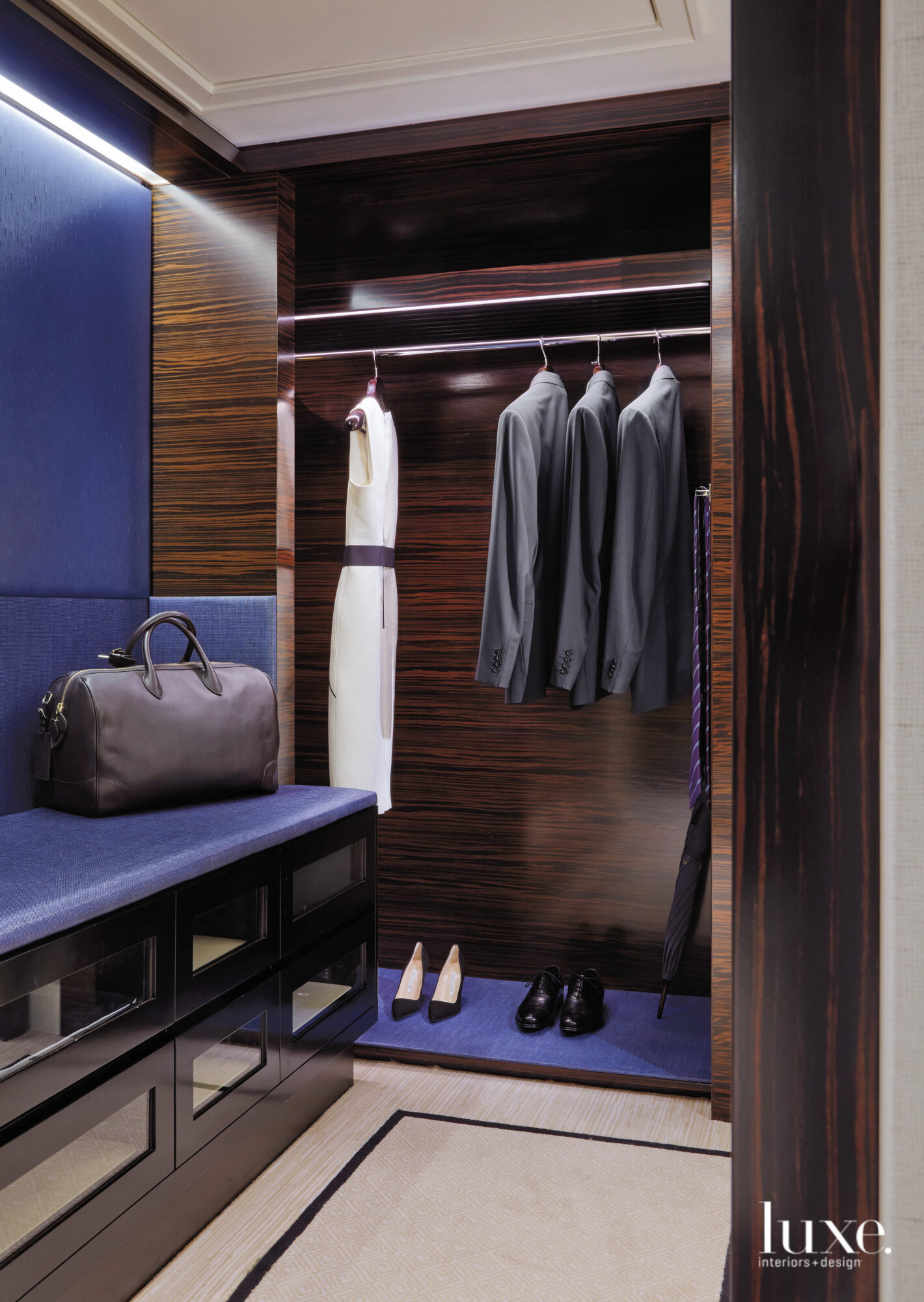 Professional attire rests in a polished wood-finished coat closet.