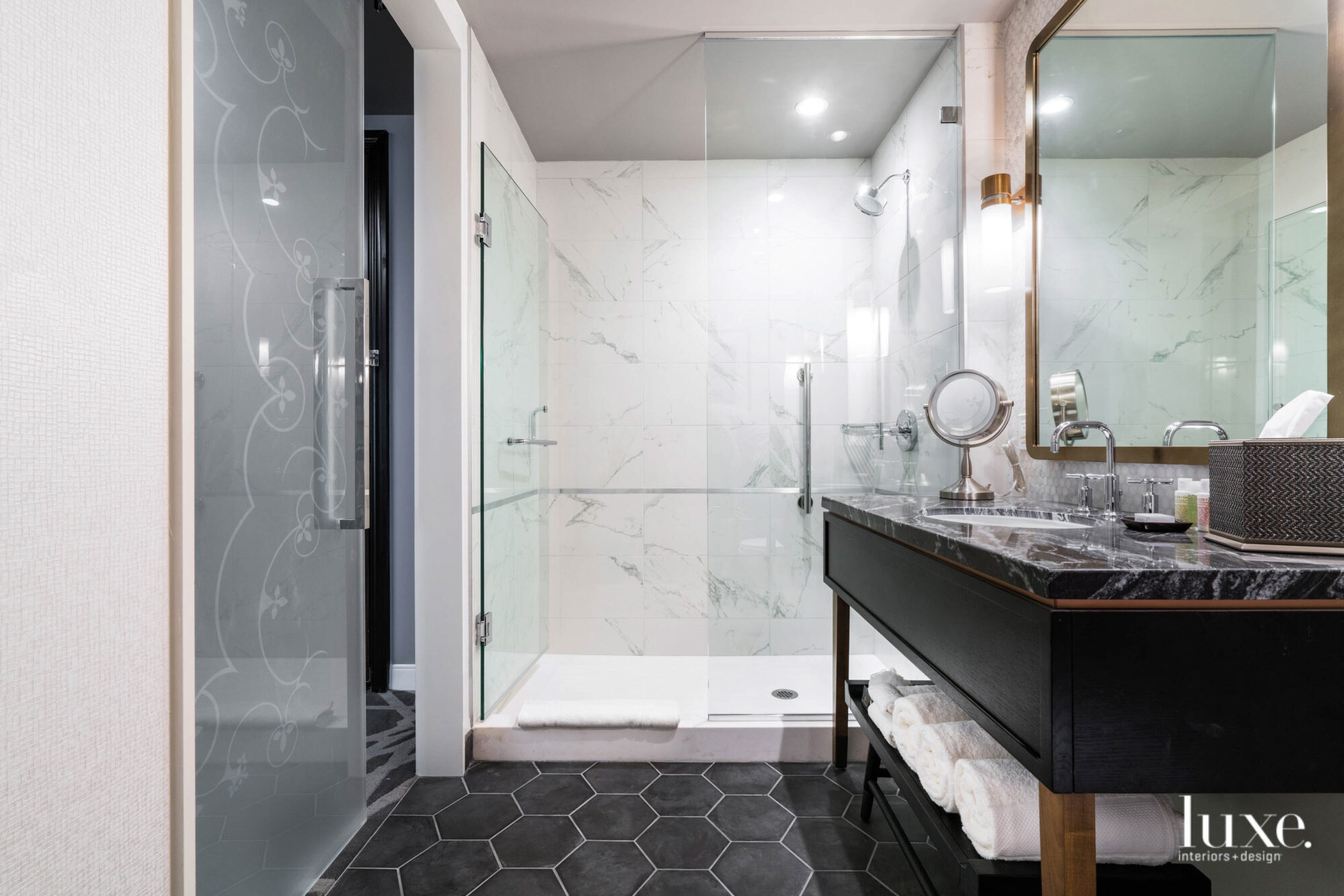 A gleaming bathroom with a marble countertop and a hexagonal tiled floor.