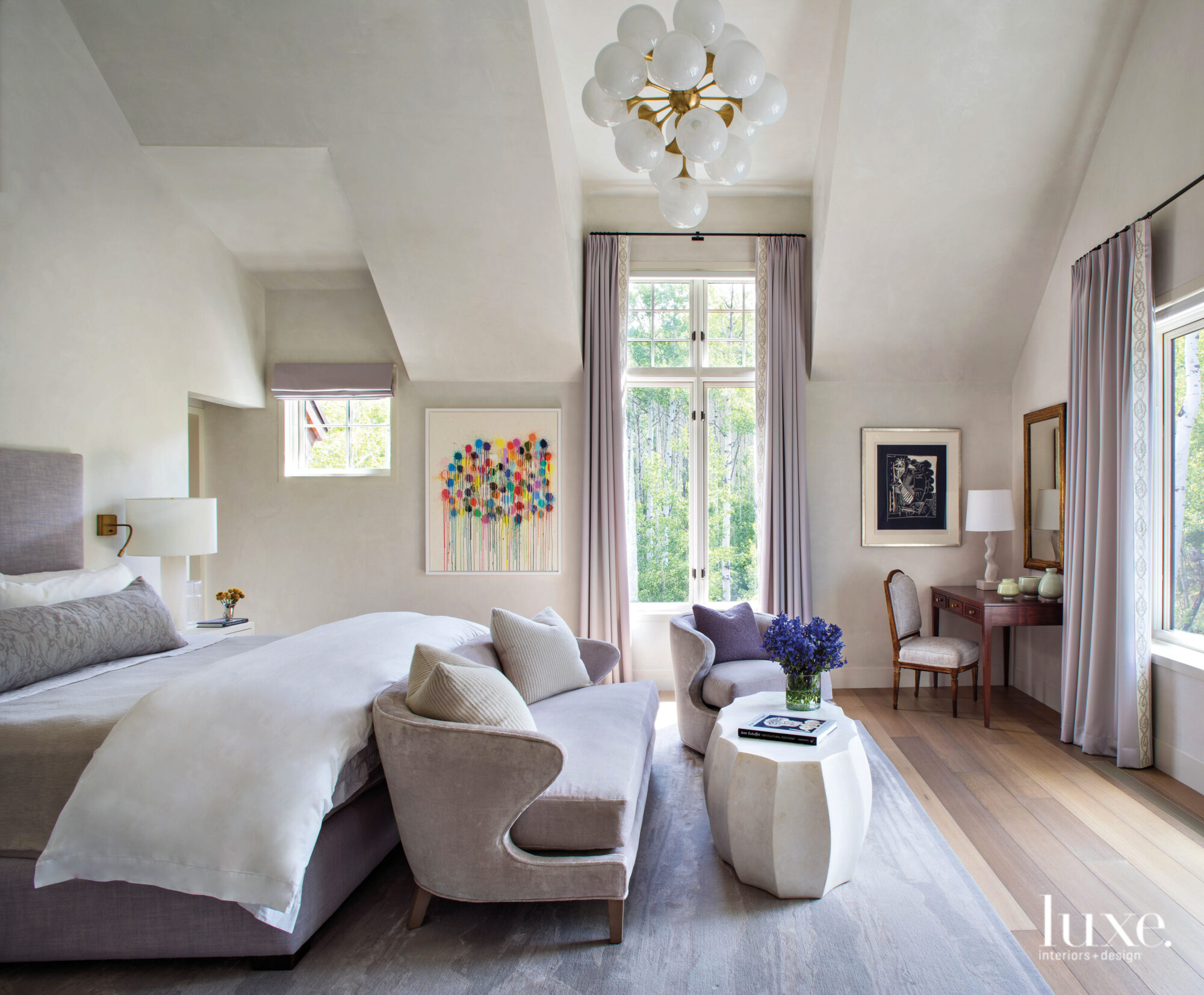 A light-filled bedroom has a...