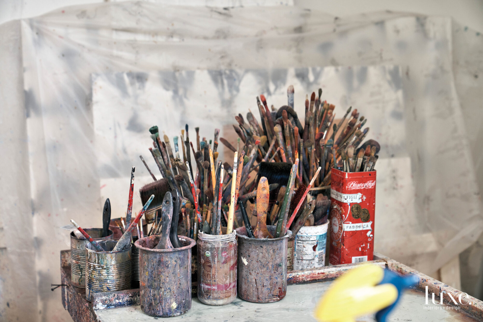 Paintbrushes fill paint-dapped containers.