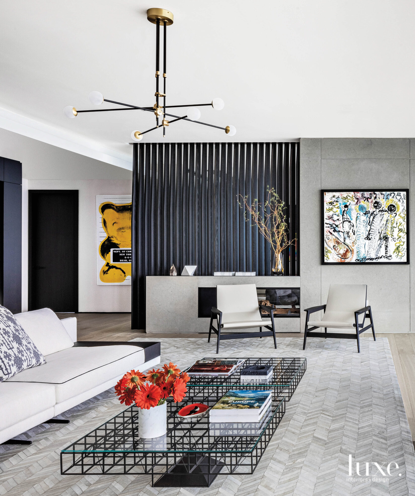 Living room of a Miami high-rise with black and gold light fixture and metal coffee tables
