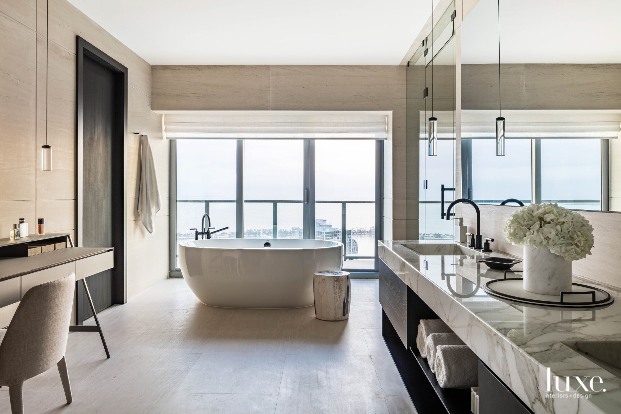 A neutral-toned bathroom with a...