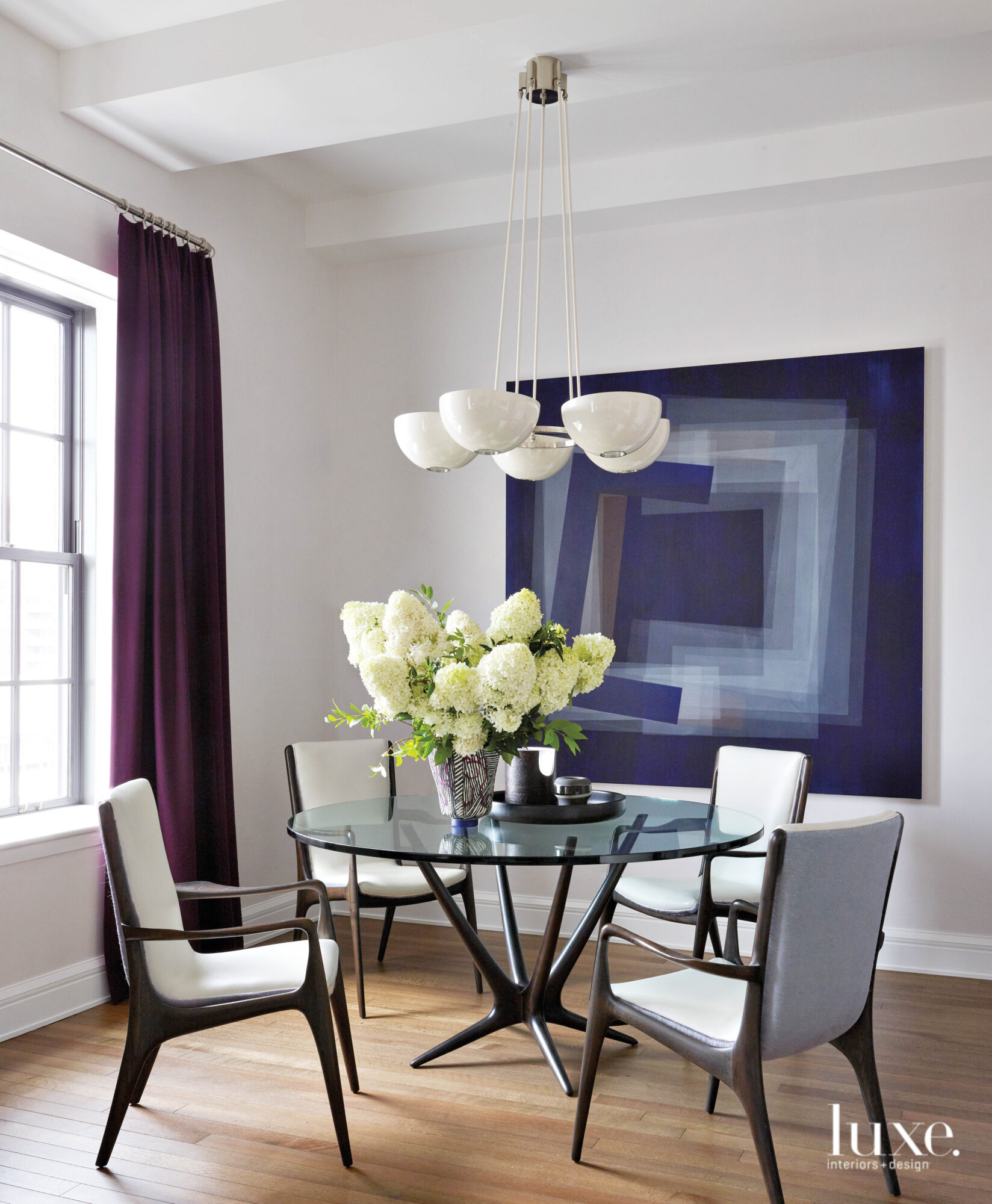 Dark blue decor surrounds a clear, round dining room table