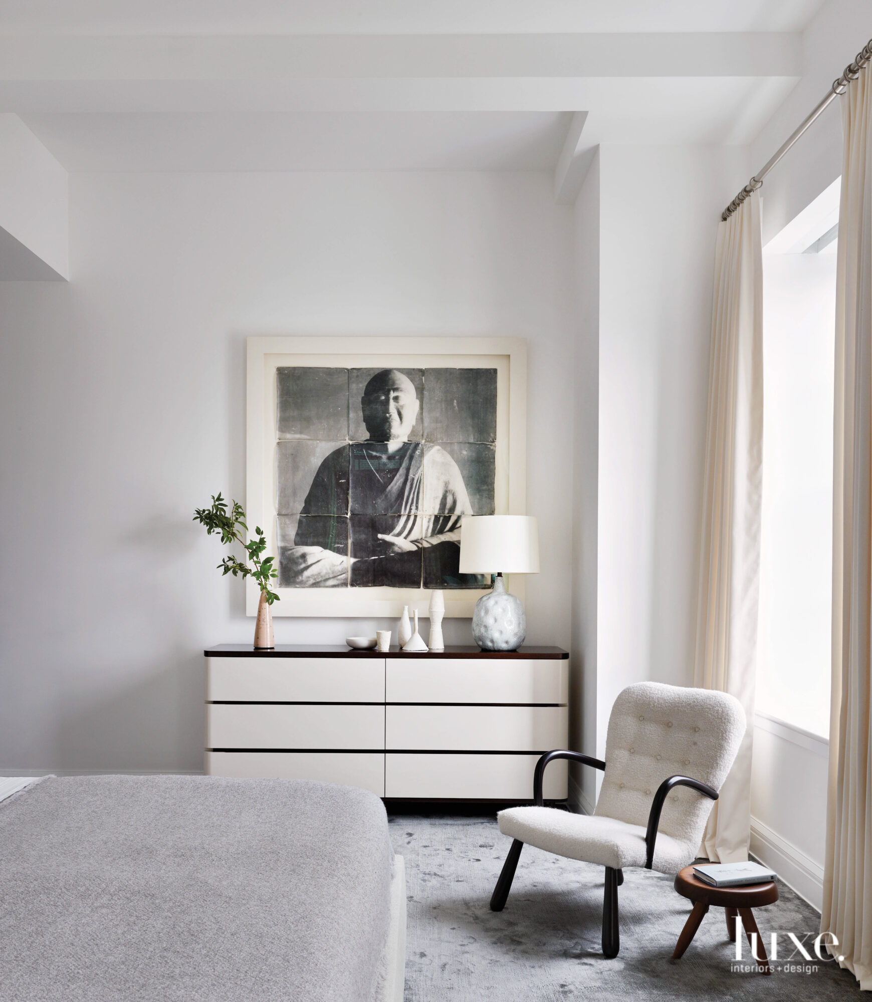 An all-white master bedroom promotes...