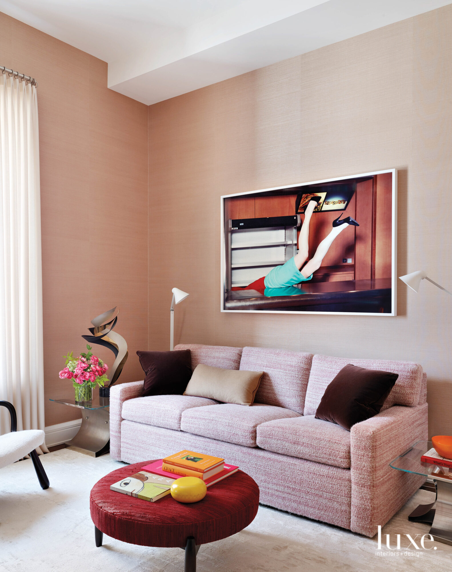 The color pink takes center stage as the sofa and wall color in this office space