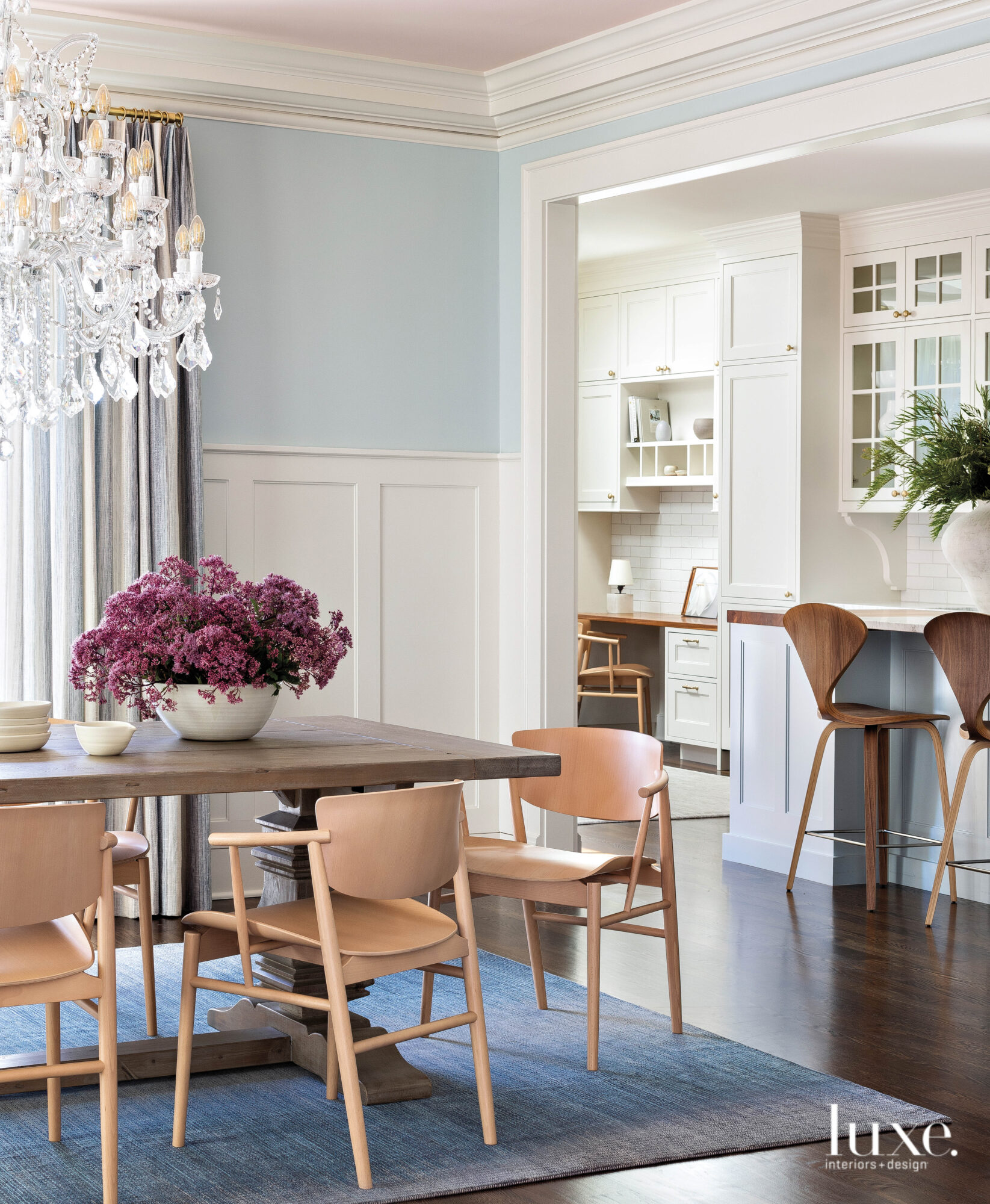 Detail shot of blue-painted dining room with a grand, crystal chandelier and wooden chairs.