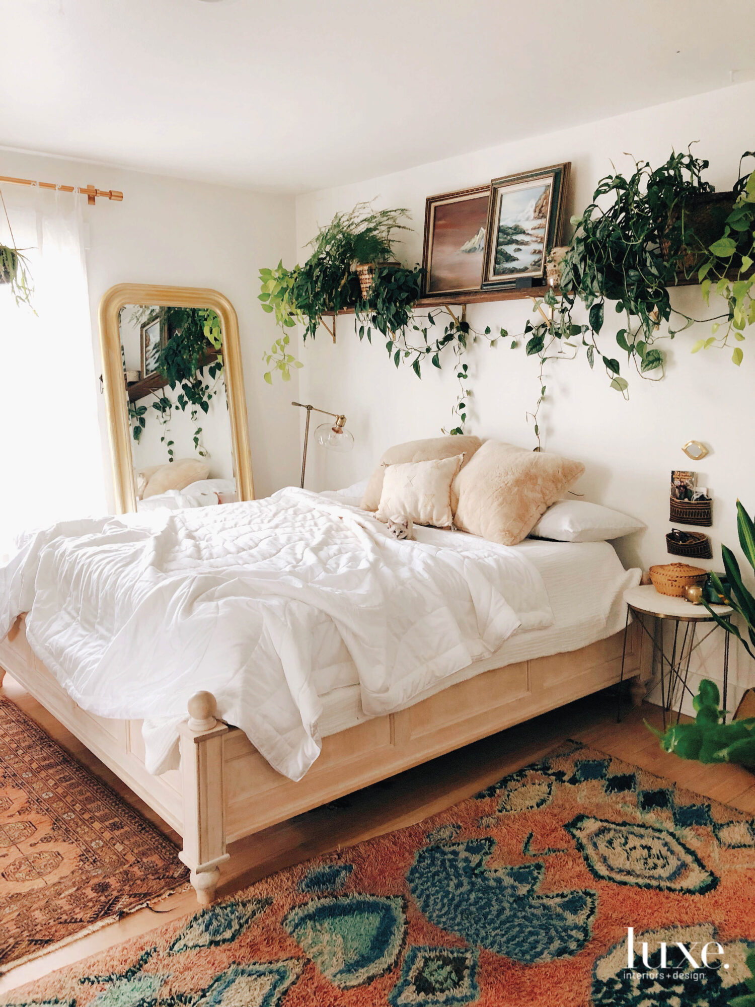A peach and white colored bedspread is framed with dark green plants all over