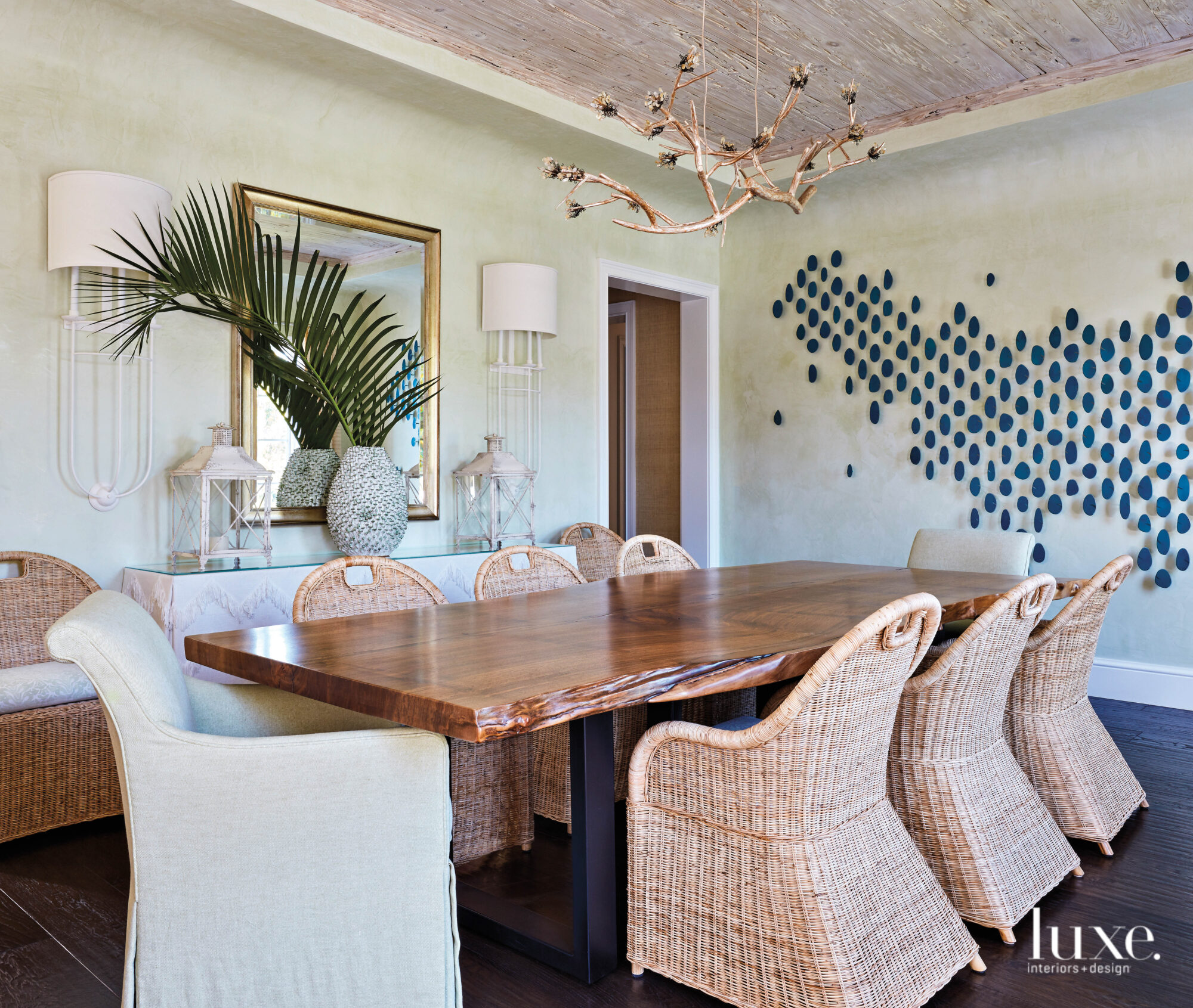 Dining room with light green walls, pecky cypress ceiling and rattan chairs.
