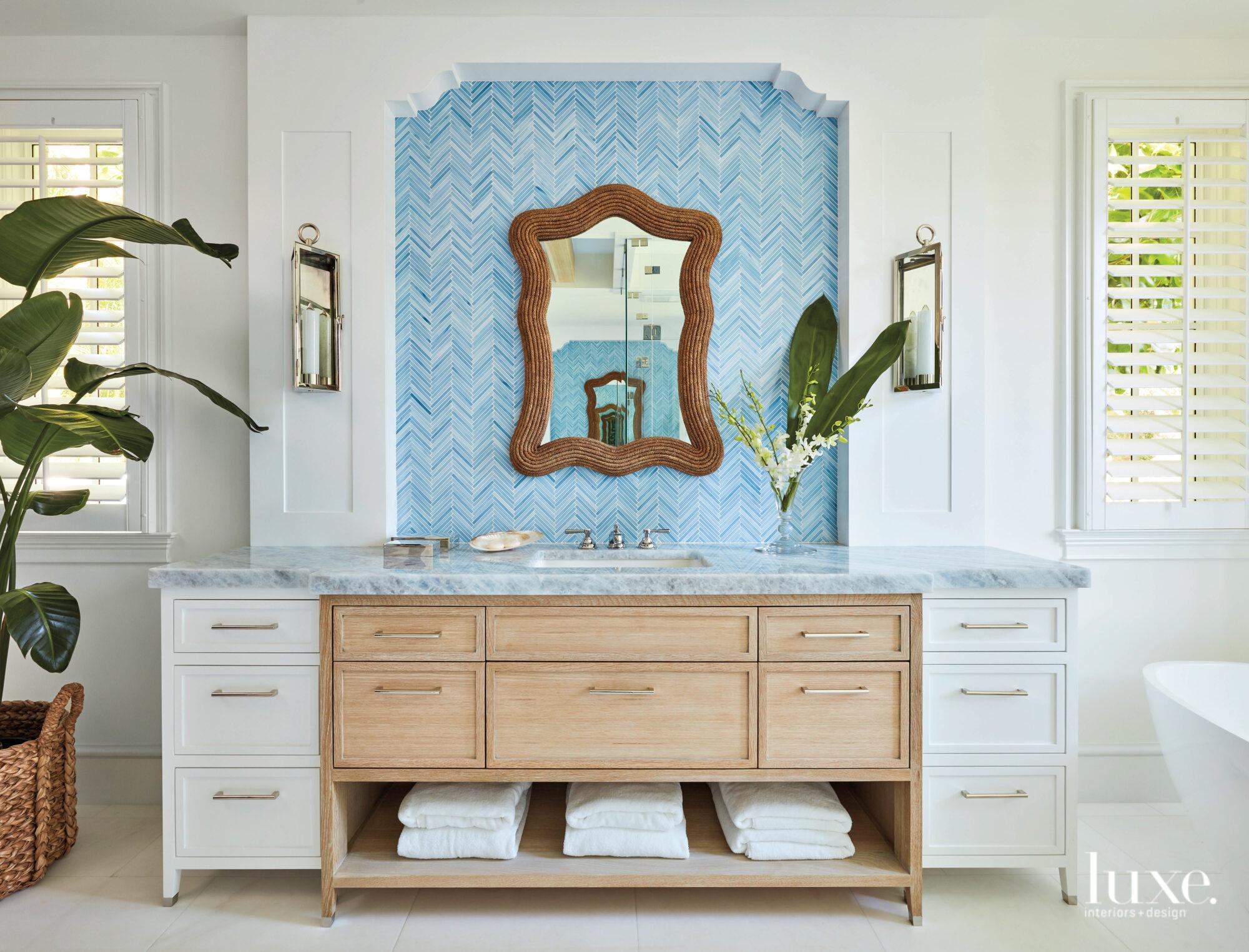 Bathroom with wood-frame mirror hung...