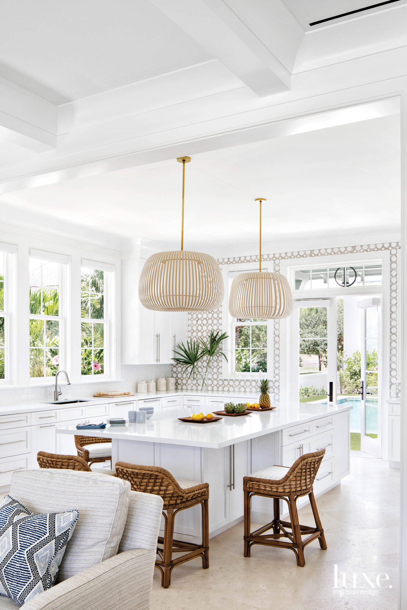 White kitchen with pendant lights made of cotton strips and seagrass stools.