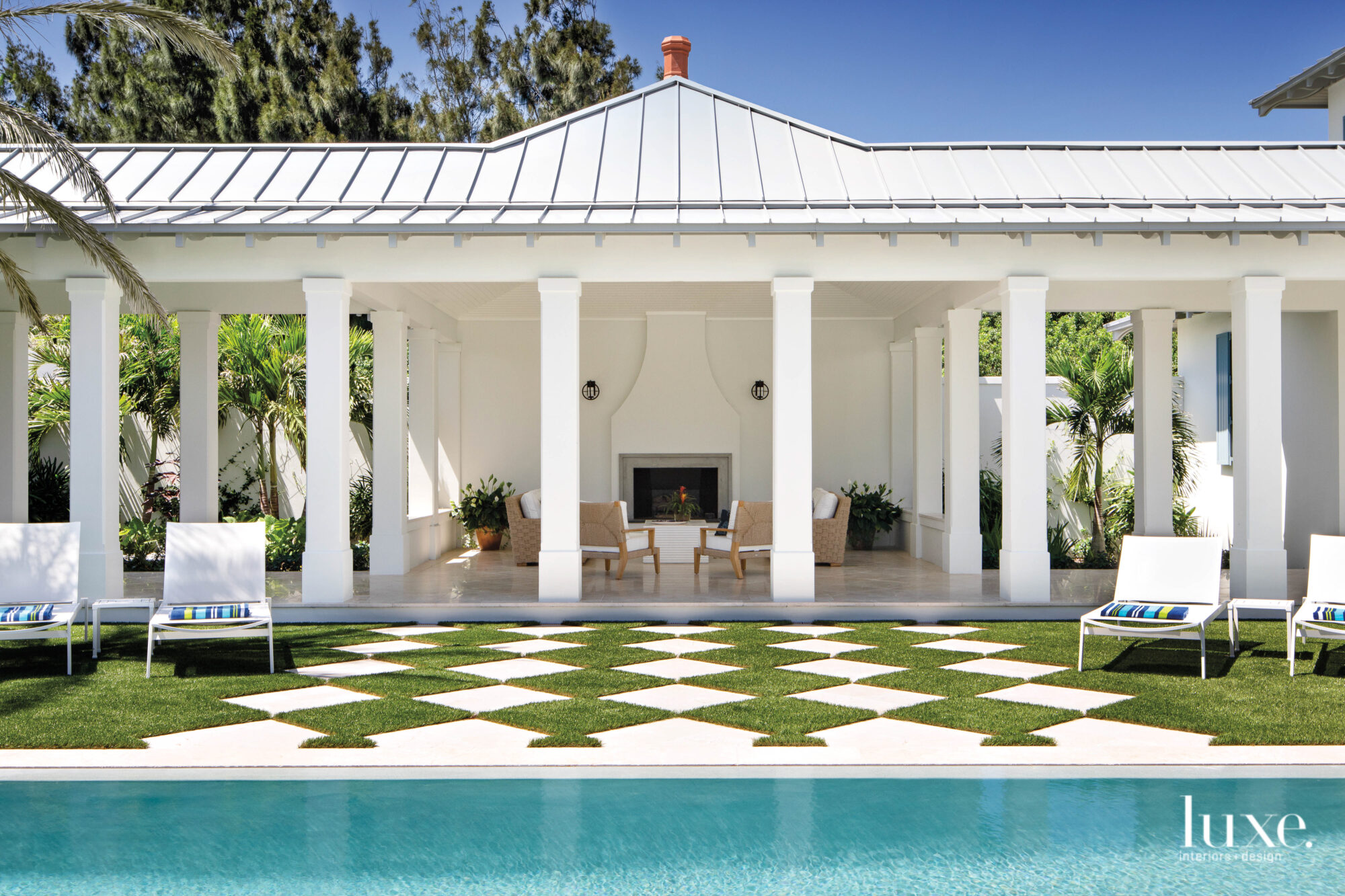Pool courtyard with covered loggia and checkerboard of turf and hardscape.