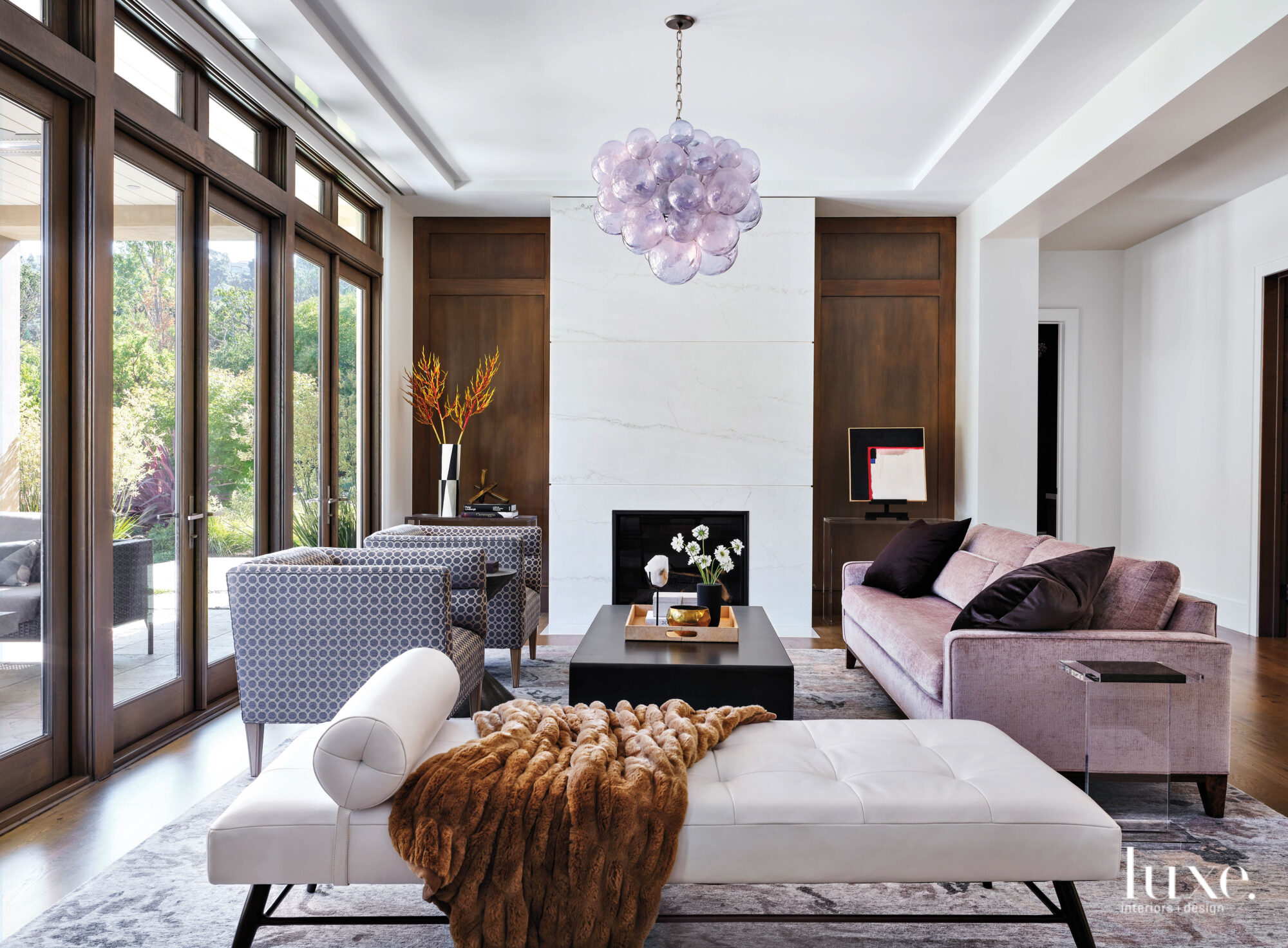 A rose colored sofa and chairs and a creamy chaise gather around a fireplace.
