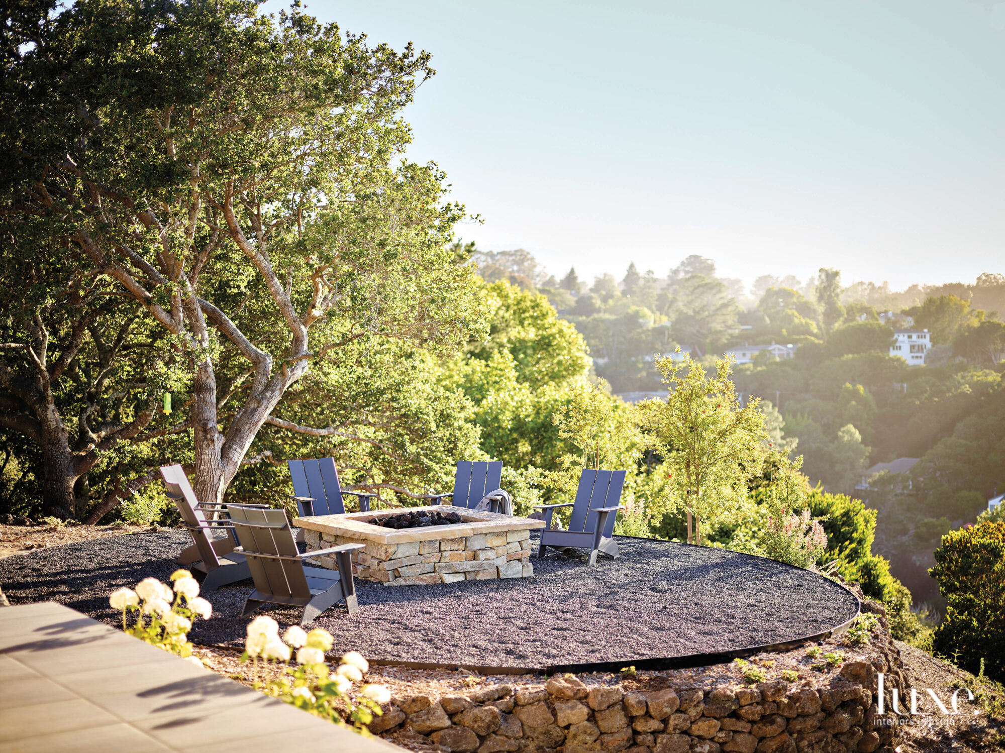 A fire pit area is placed on a hillside, it has a tree-filled view.