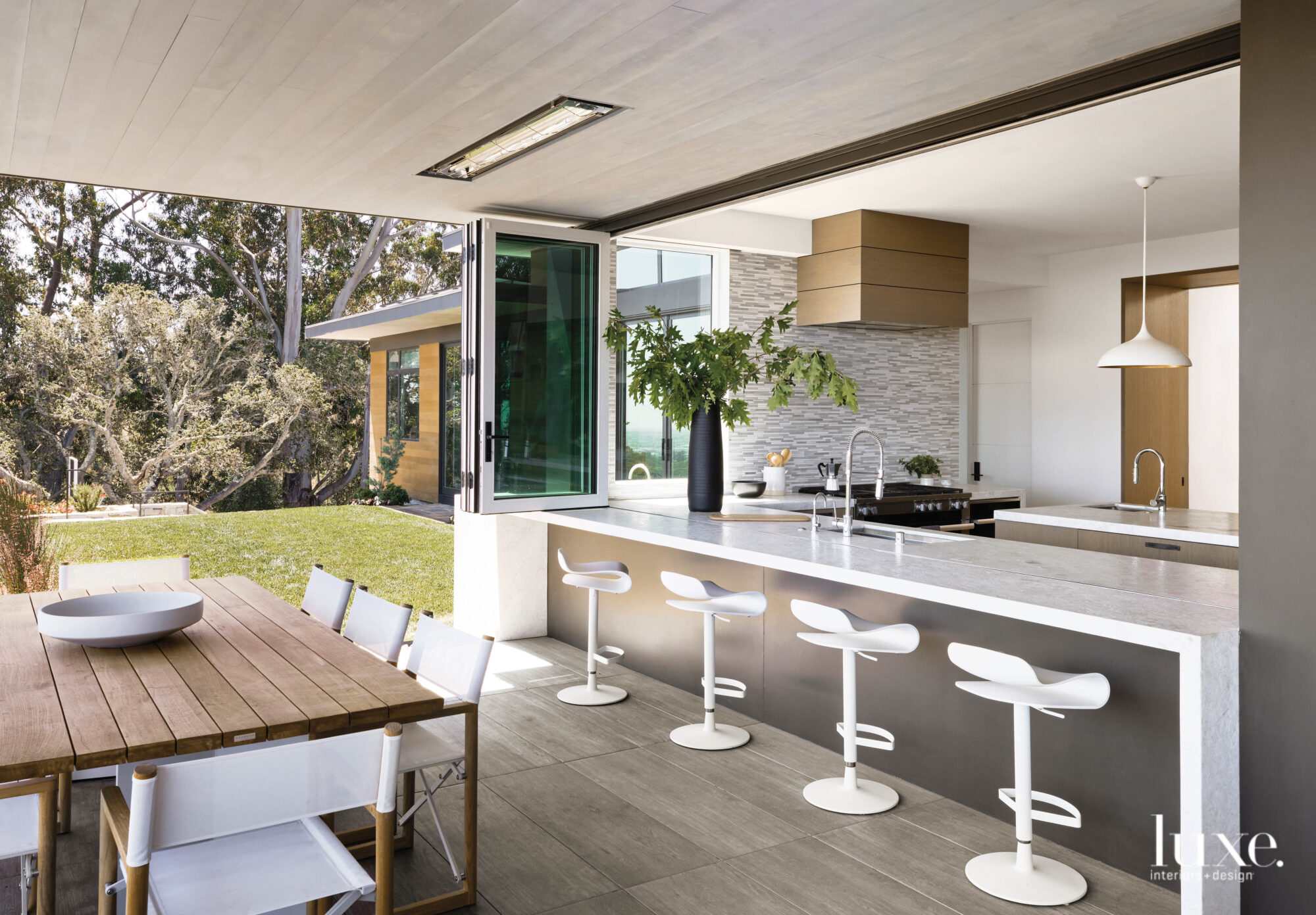 A large accordion window opens the kitchen to an outdoor dining room.