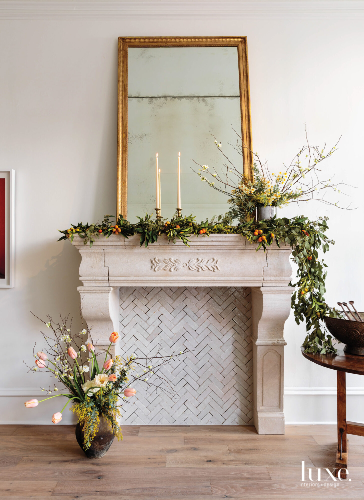 A fireplace mantel is decorated by a garland.