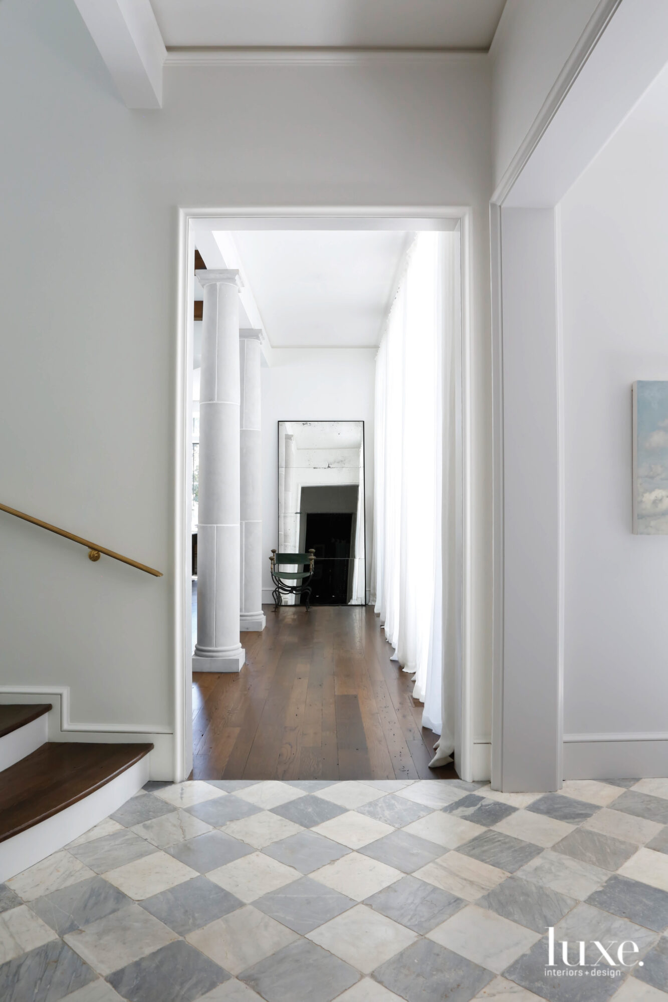 Stair hall leading to long hallway with columns on the left, drapery panels on the right and a leaning tall mirror at center