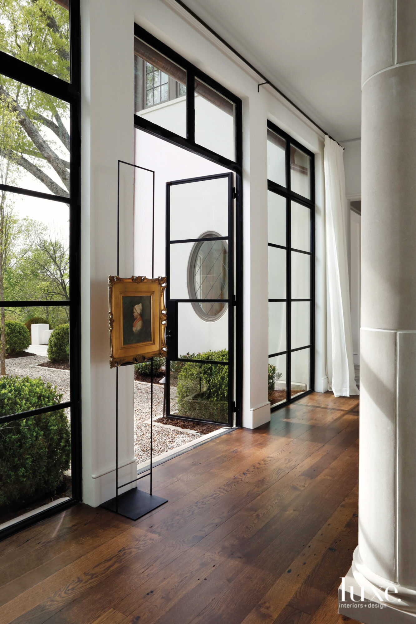 Dark wood floors and steel French doors lead to a breezy courtyard with pea gravel and clipped boxwoods