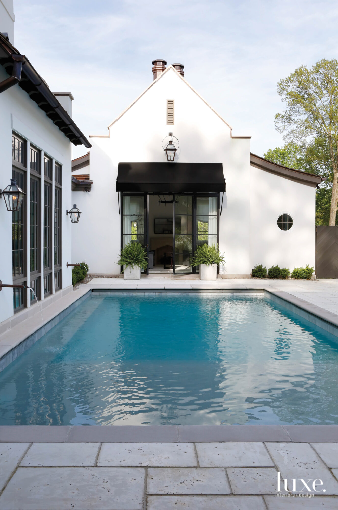 Casement windows, positioned directly against an outdoor pool and terrace, open doors to a home office in the background