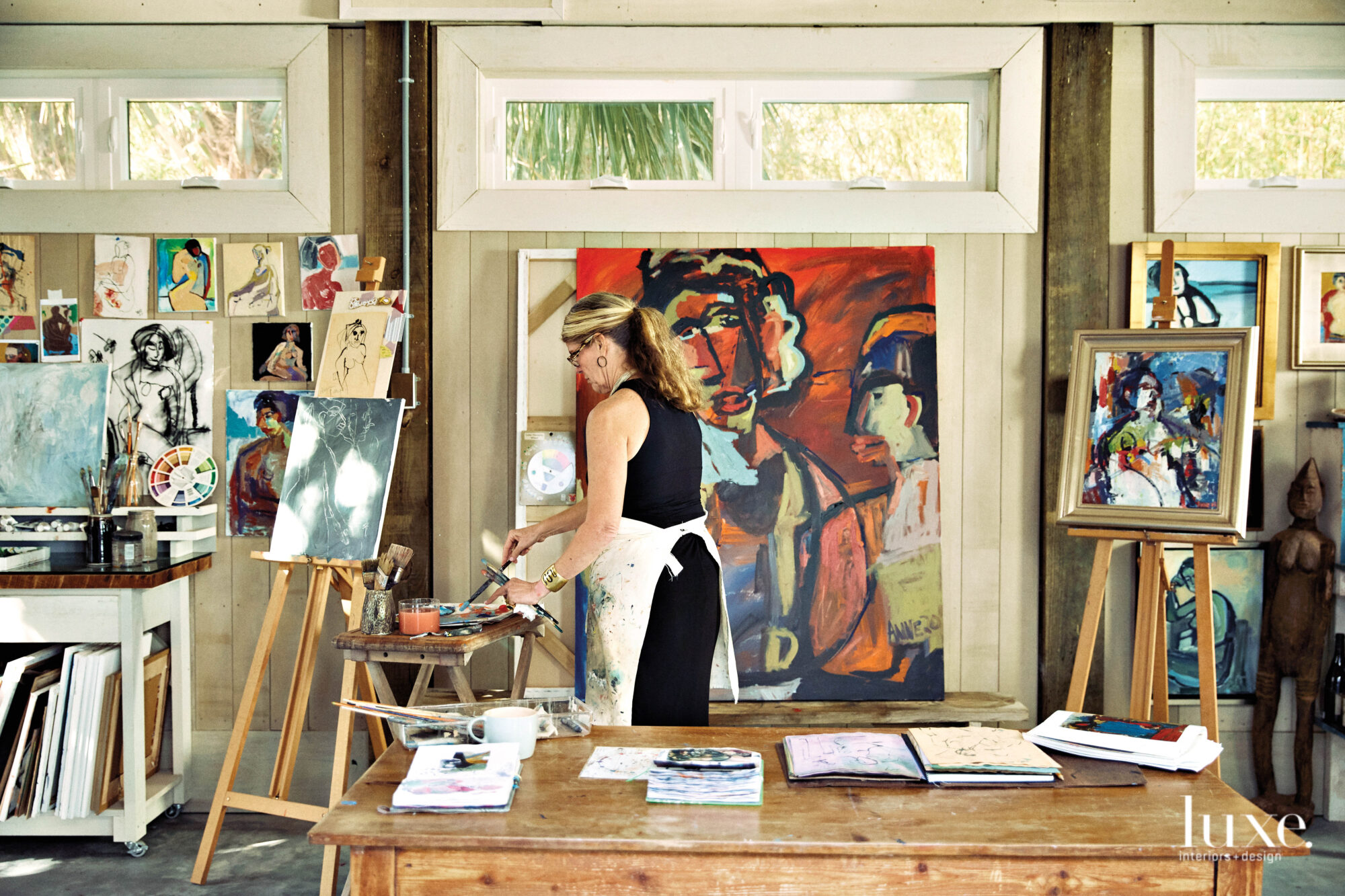 Woman standing and painting, easel with artworks to left and table in foreground
