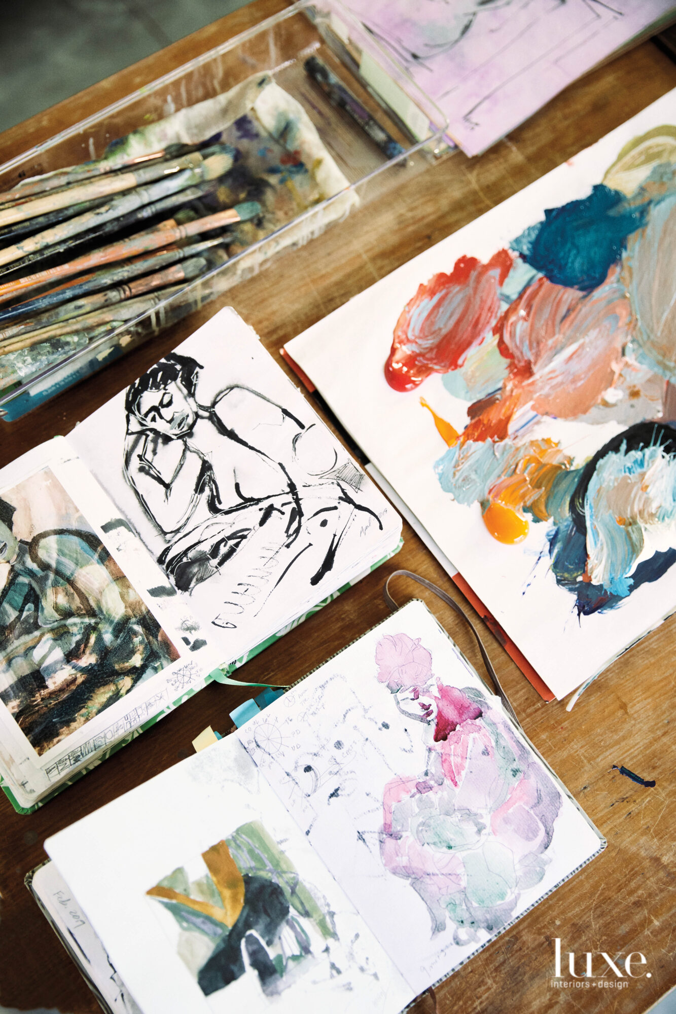 Studies of figurative paintings in small notebooks, a collection of paintbrushes, a makeshift palette topped with mixed pigments