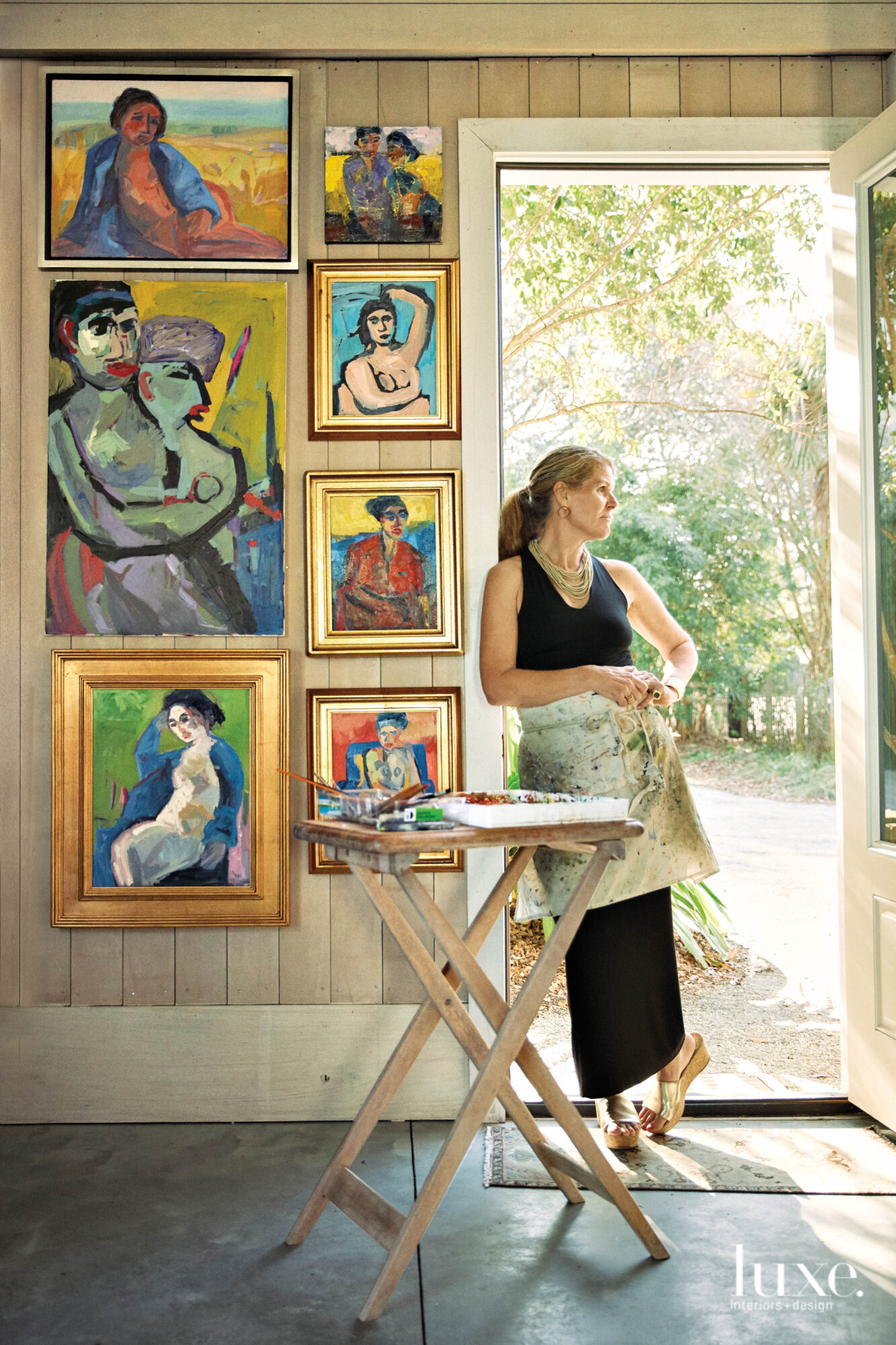 Woman wearing half apron, leaning against door frame, paintings on wall and folding table in foreground