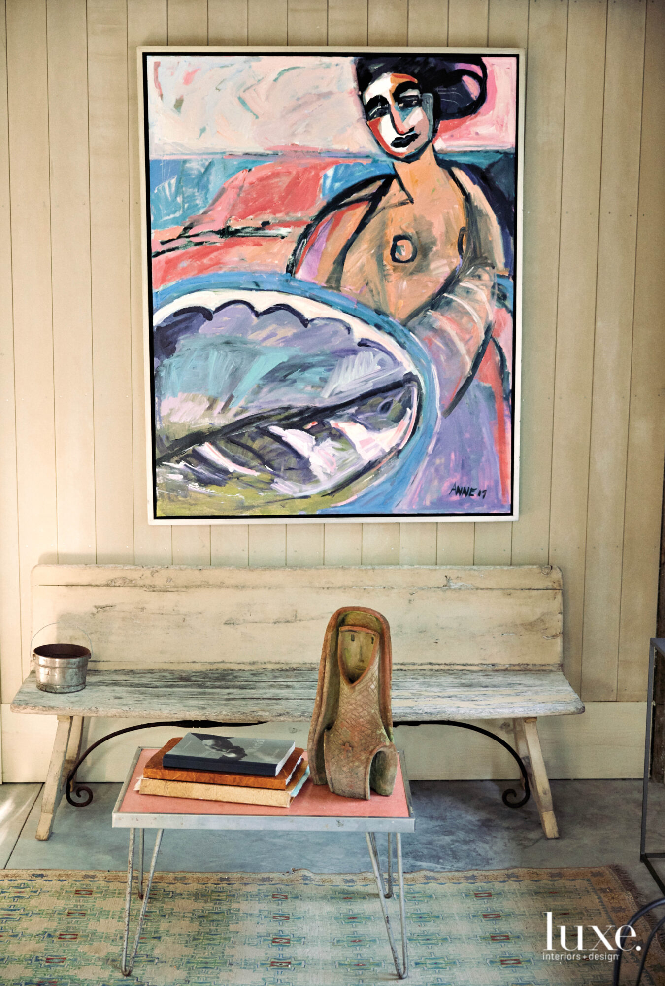 Bench with figurative painting on the paneled wall above it