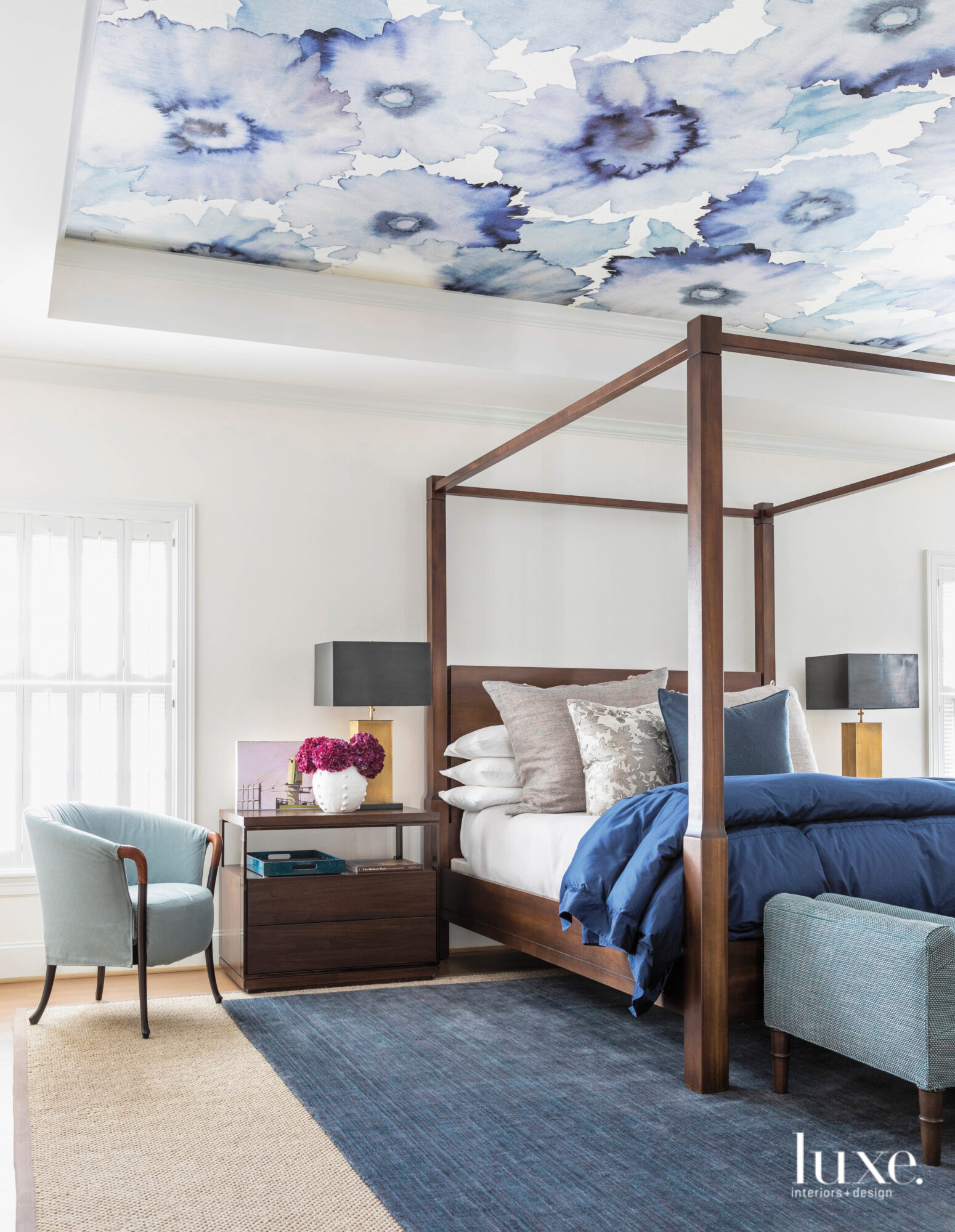 Blue-hued master bedroom with wallpapered...