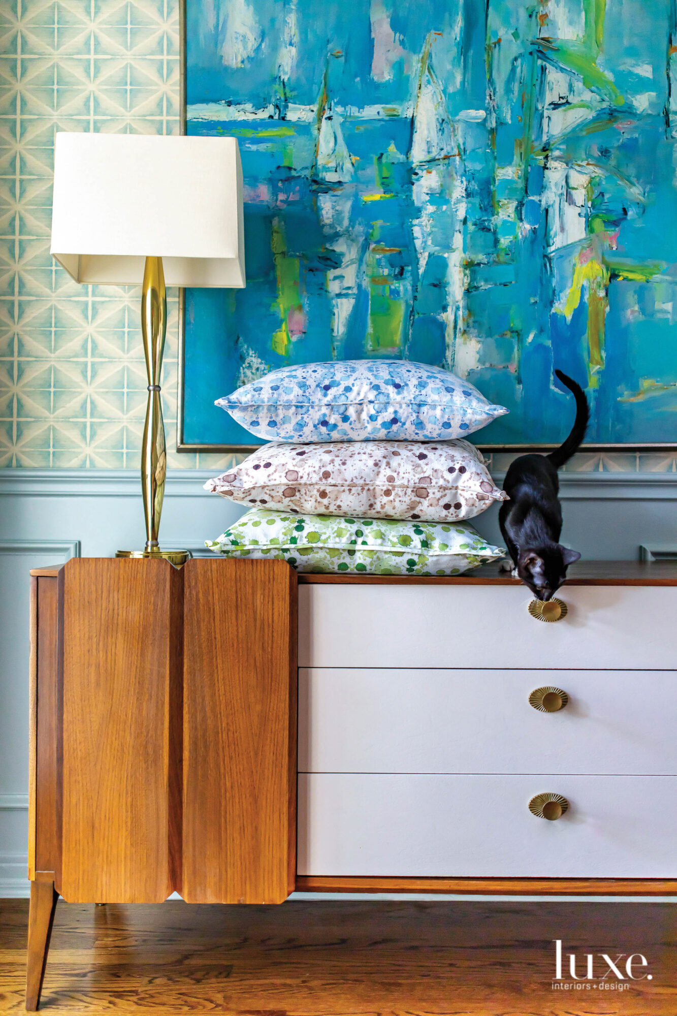 Tri-colored pillows are stacked on a dresser in front of a bright blue art piece