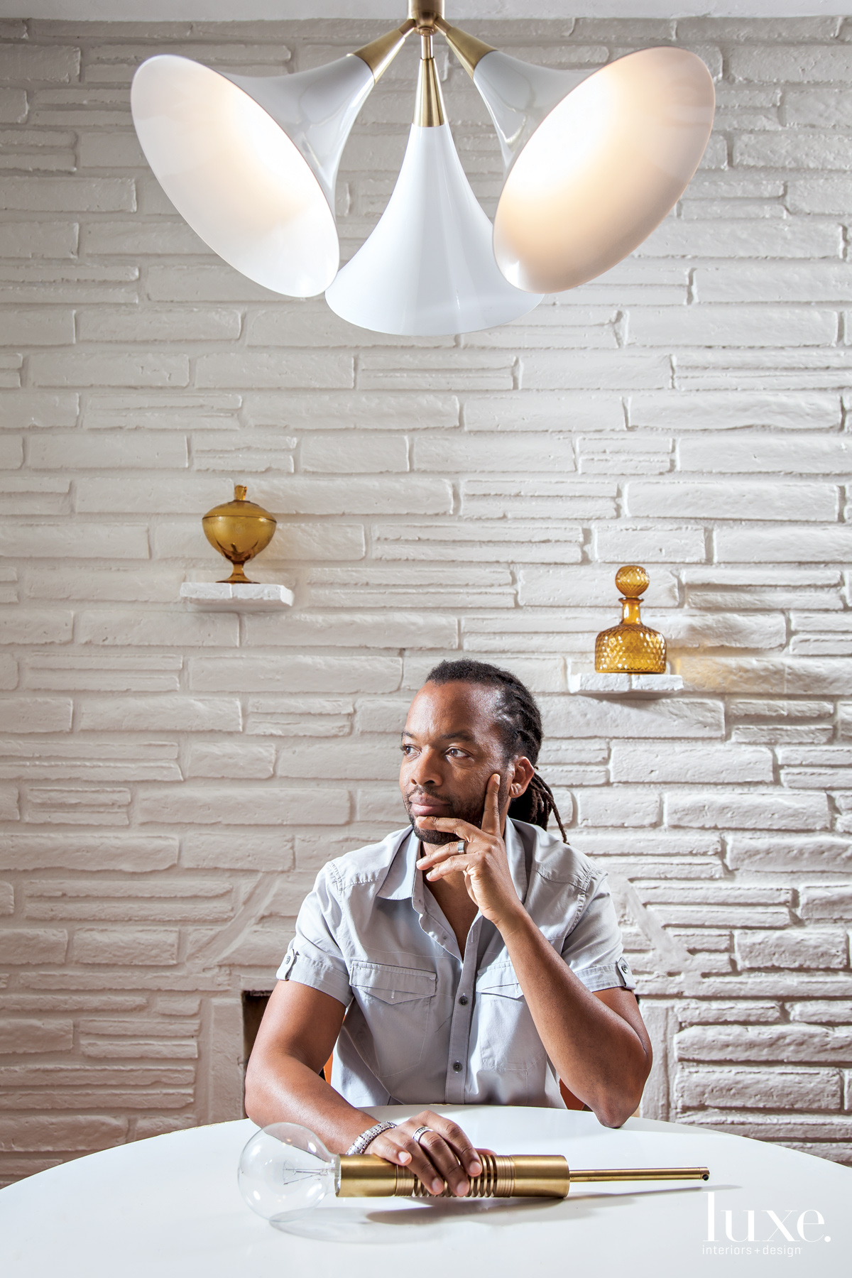 Lighting designer Raymond Barberousse sits among some of his creations.