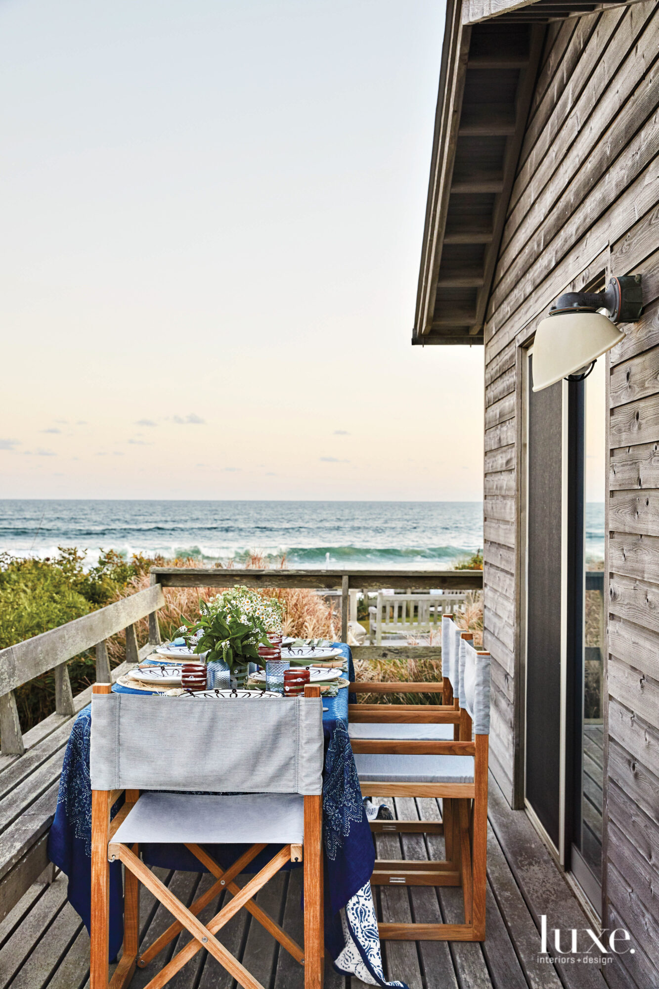 An ocean view lies beyond a set table in the Hamptons