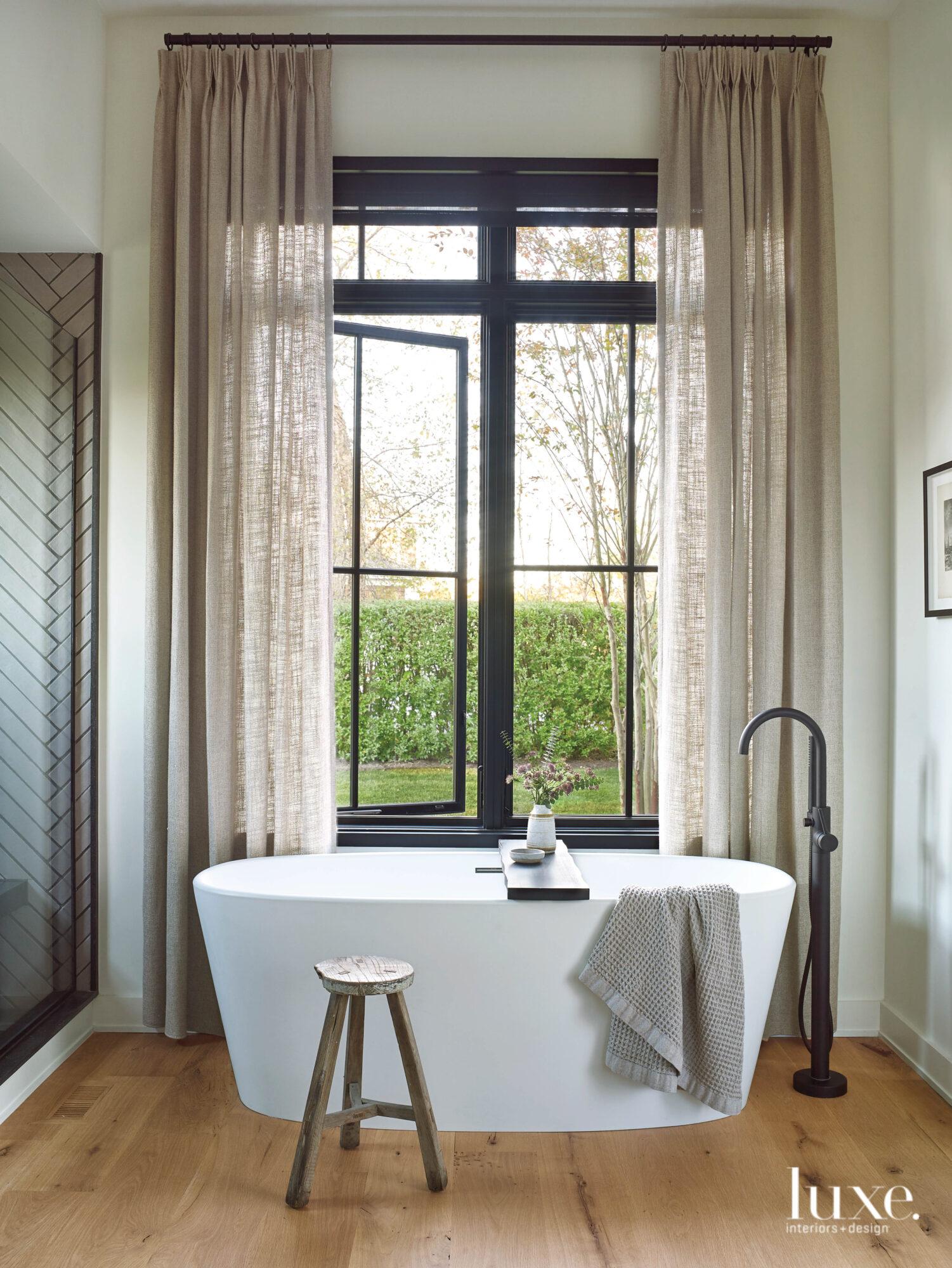 A modern white bathtub defines...