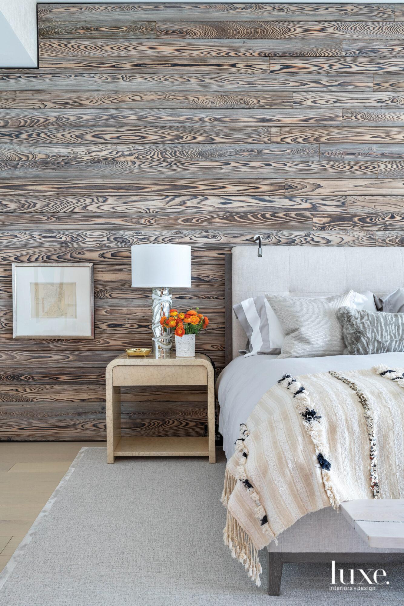 Master bedroom with wood-clad wall...