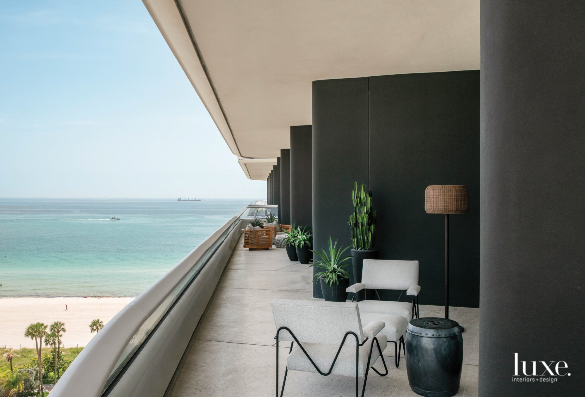Terrace with gray armchairs, plants and beach views