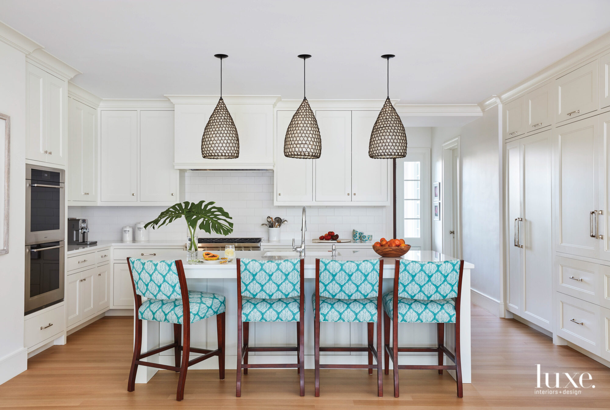 Kitchen with white cabinetry and barstools upholstered in a bright blue patterned fabric.