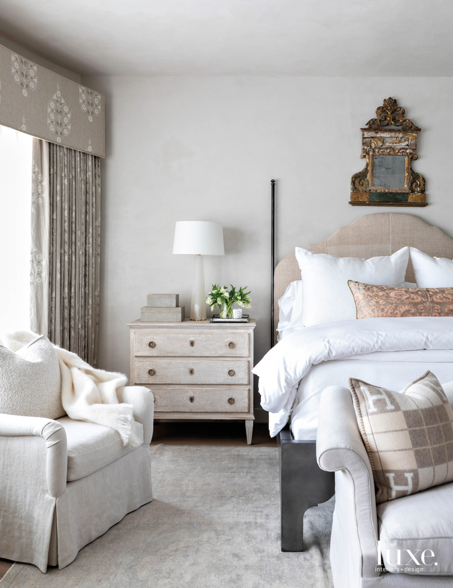 Neutral master bedroom with layered...