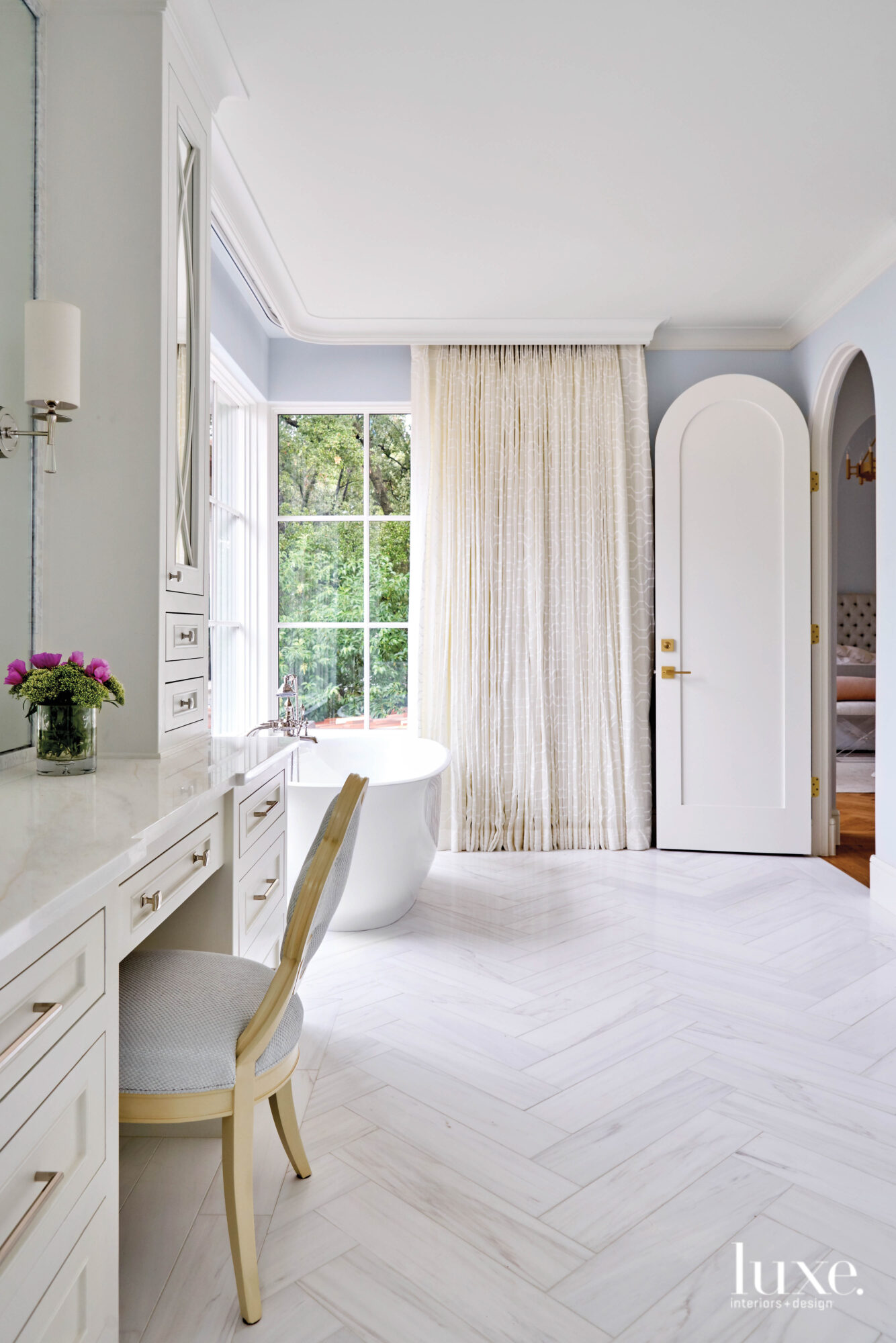 Elegant master bathroom with herringbone...