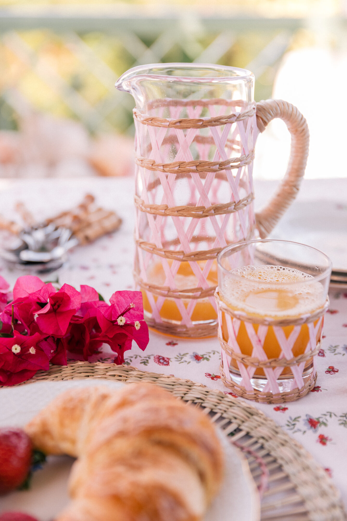 Blush-colored, rattan-detailed cups and pitchers dot the table
