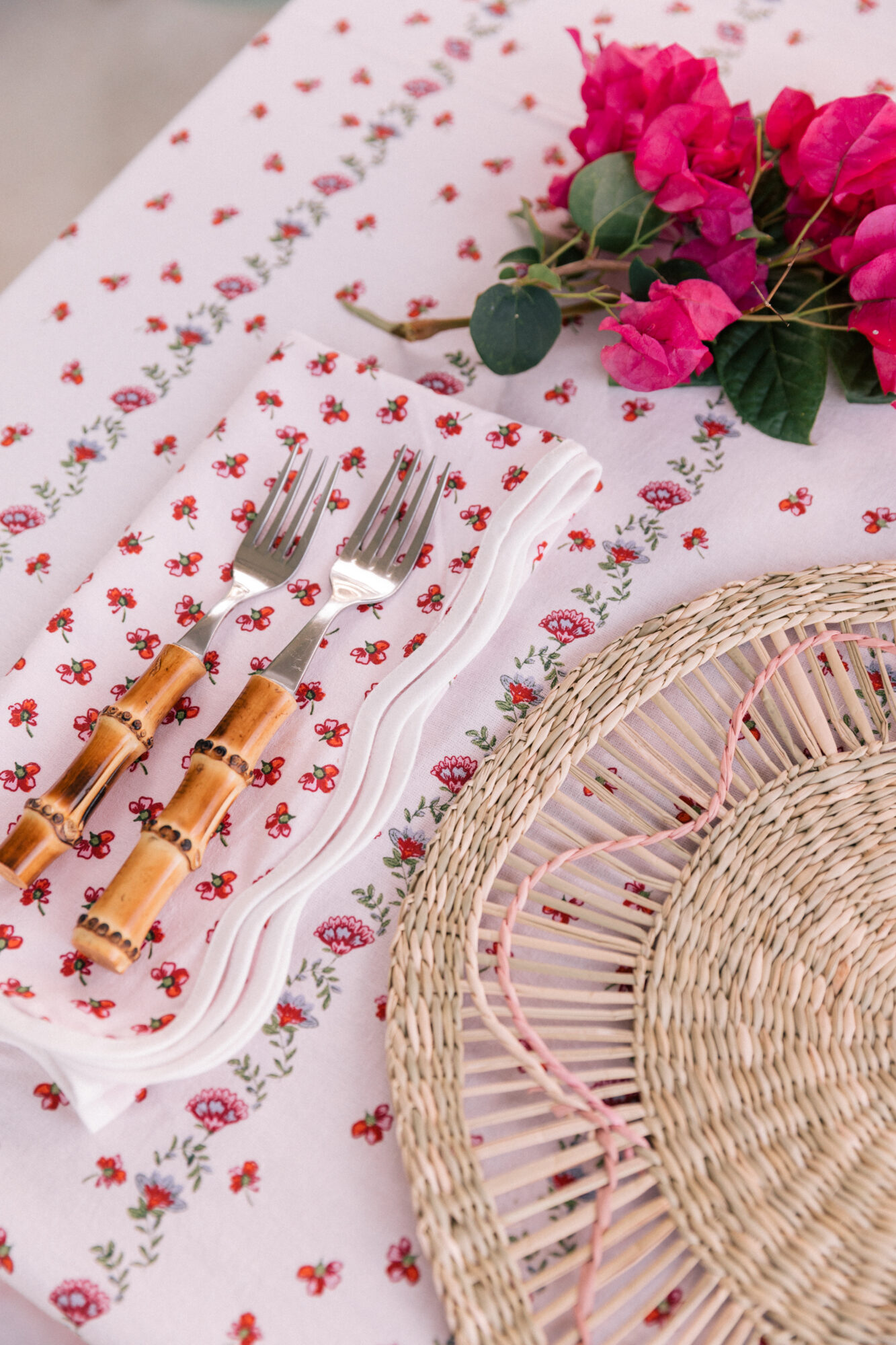 A rattan-detailed place-mat sits atop a colorful, floral tablecloth