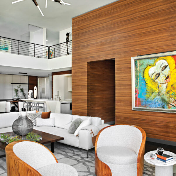 In Arizona, A Clear Vision Leads To Design That Celebrates Modern Art And Mountain Views The double-height living room with a modern painting by Jamali hanging on a wood veneer wall.