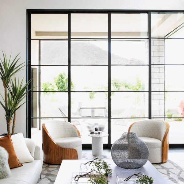 In Arizona, A Clear Vision Leads To Design That Celebrates Modern Art And Mountain Views A grouping of white and wood swivel chairs in the corner of the living room.