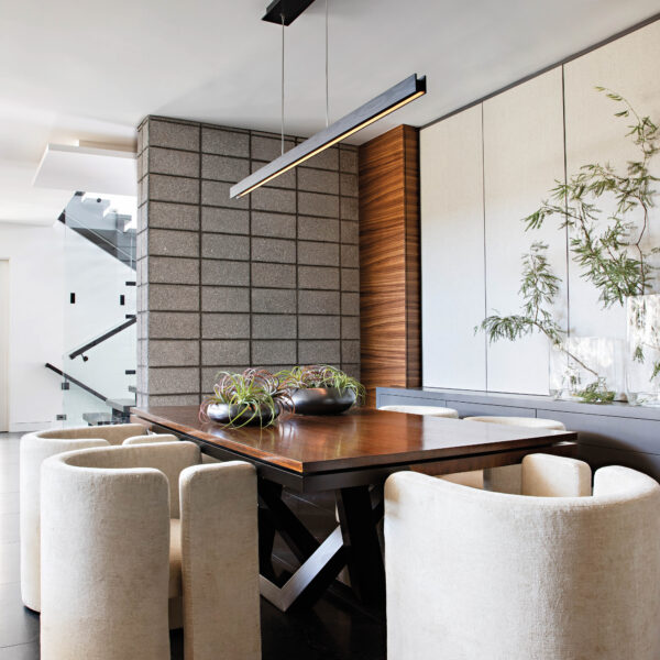 In Arizona, A Clear Vision Leads To Design That Celebrates Modern Art And Mountain Views The dining room with white curved back chairs and a wood table with a steel base.