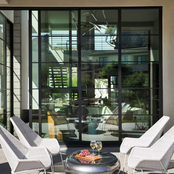 In Arizona, A Clear Vision Leads To Design That Celebrates Modern Art And Mountain Views Four white wicker chairs around a metal coffee table on the patio.