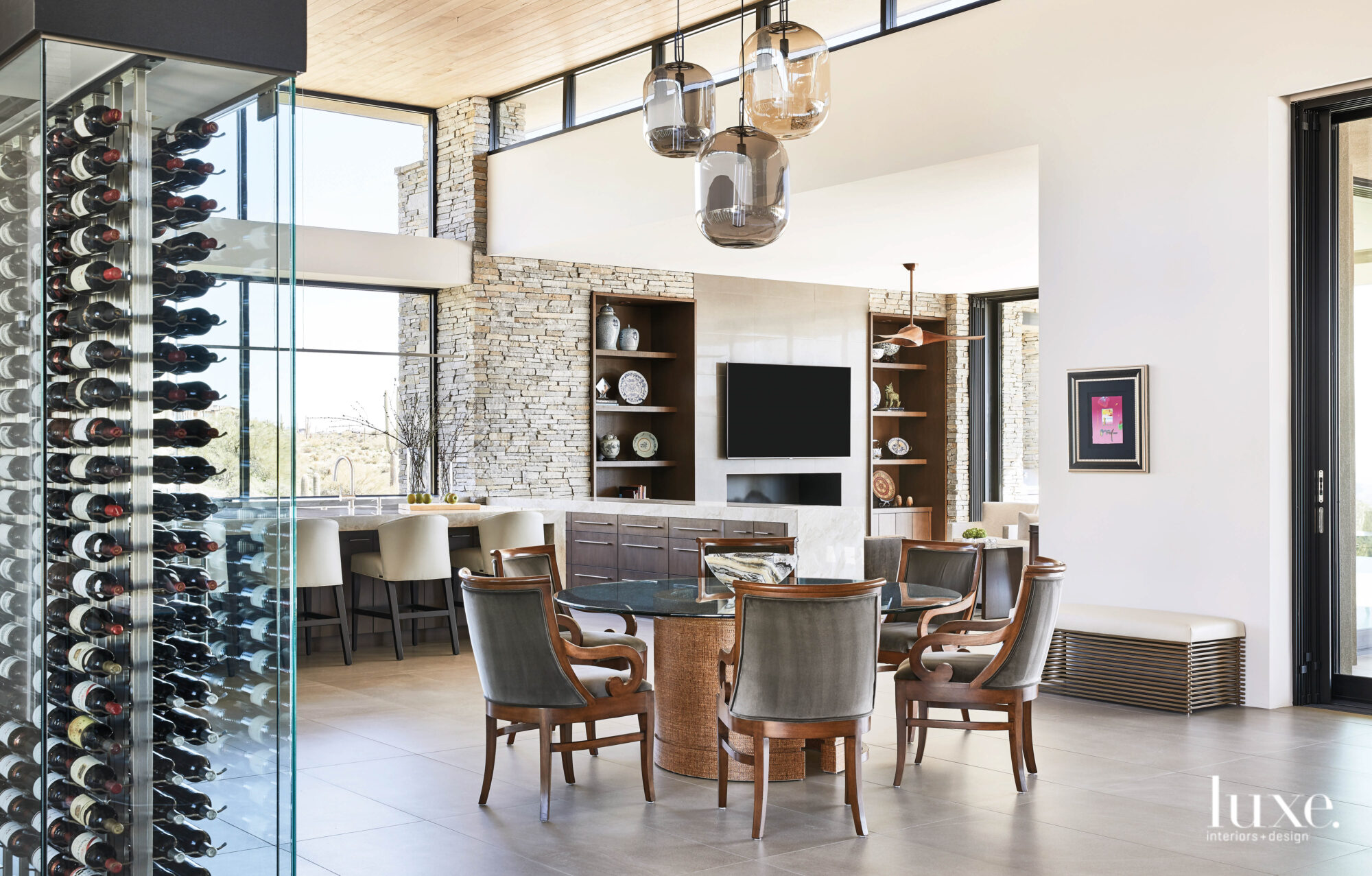 A dining area with a round glass-topped table and a smoked-glass pendant overhead sits near a glass wine wall.