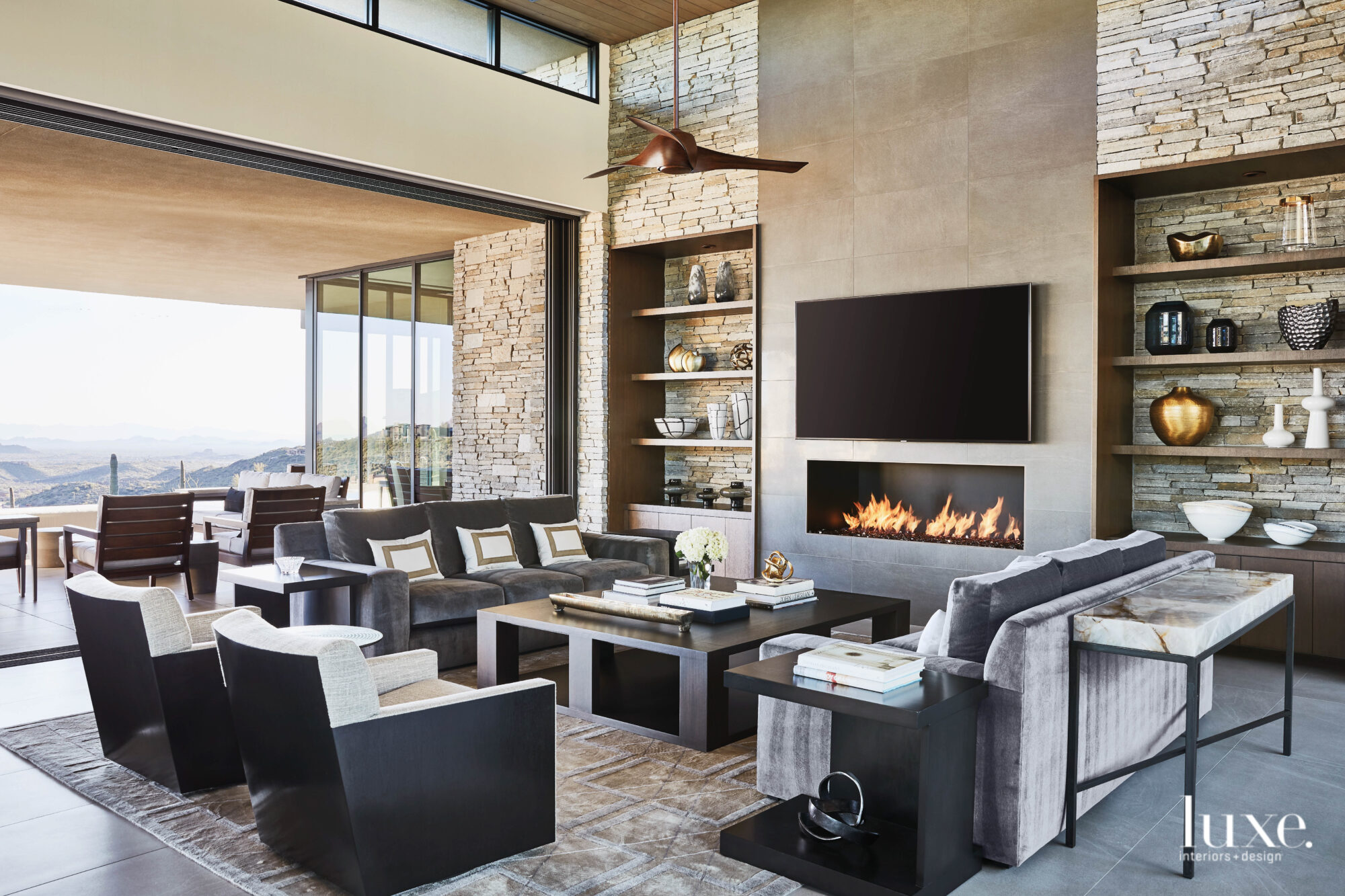 A gray-hued living area surrounds a fireplace, with further views to the mountain vistas.