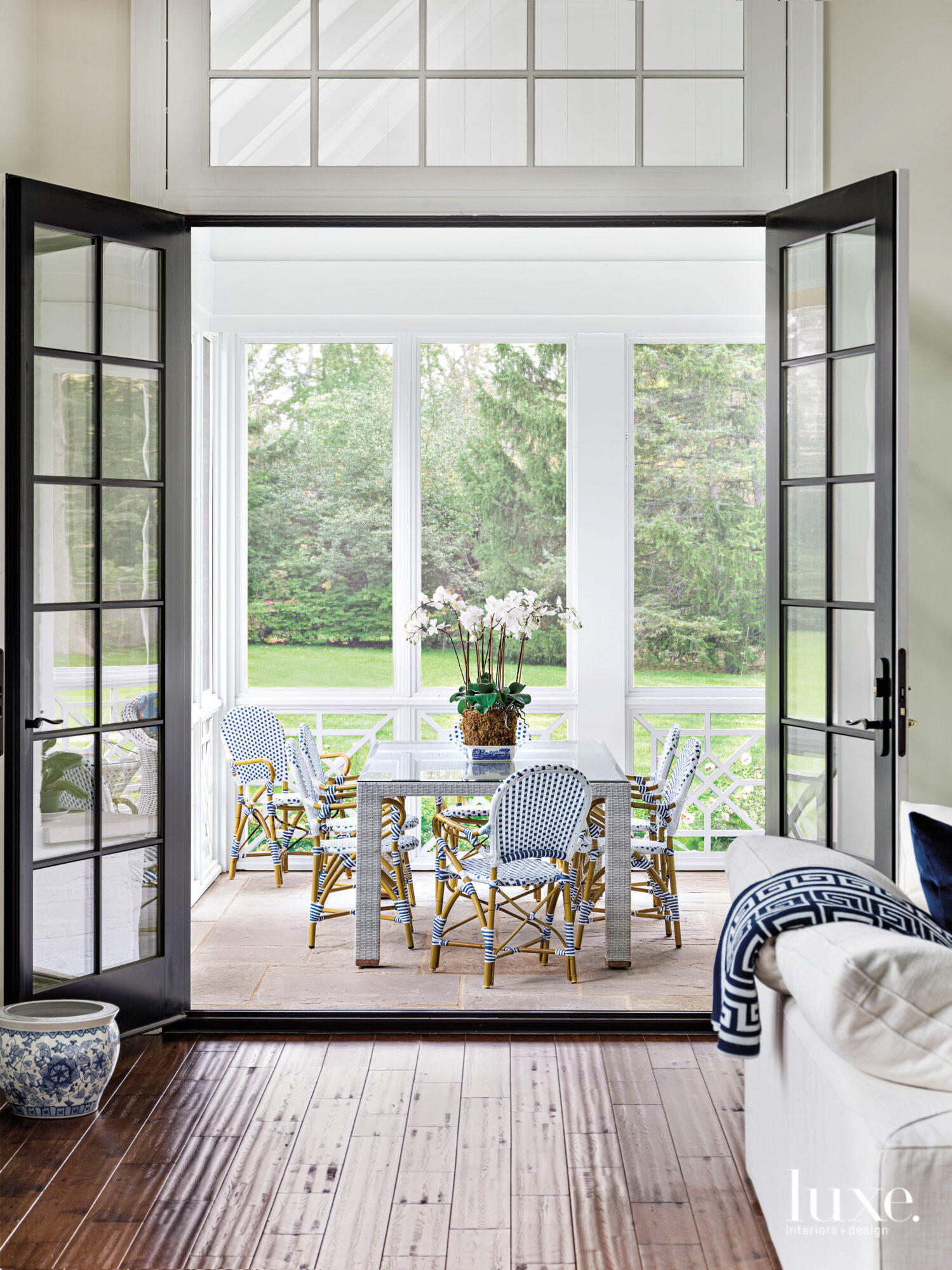 The screened-in porch with a dining table and bistro-style chairs.