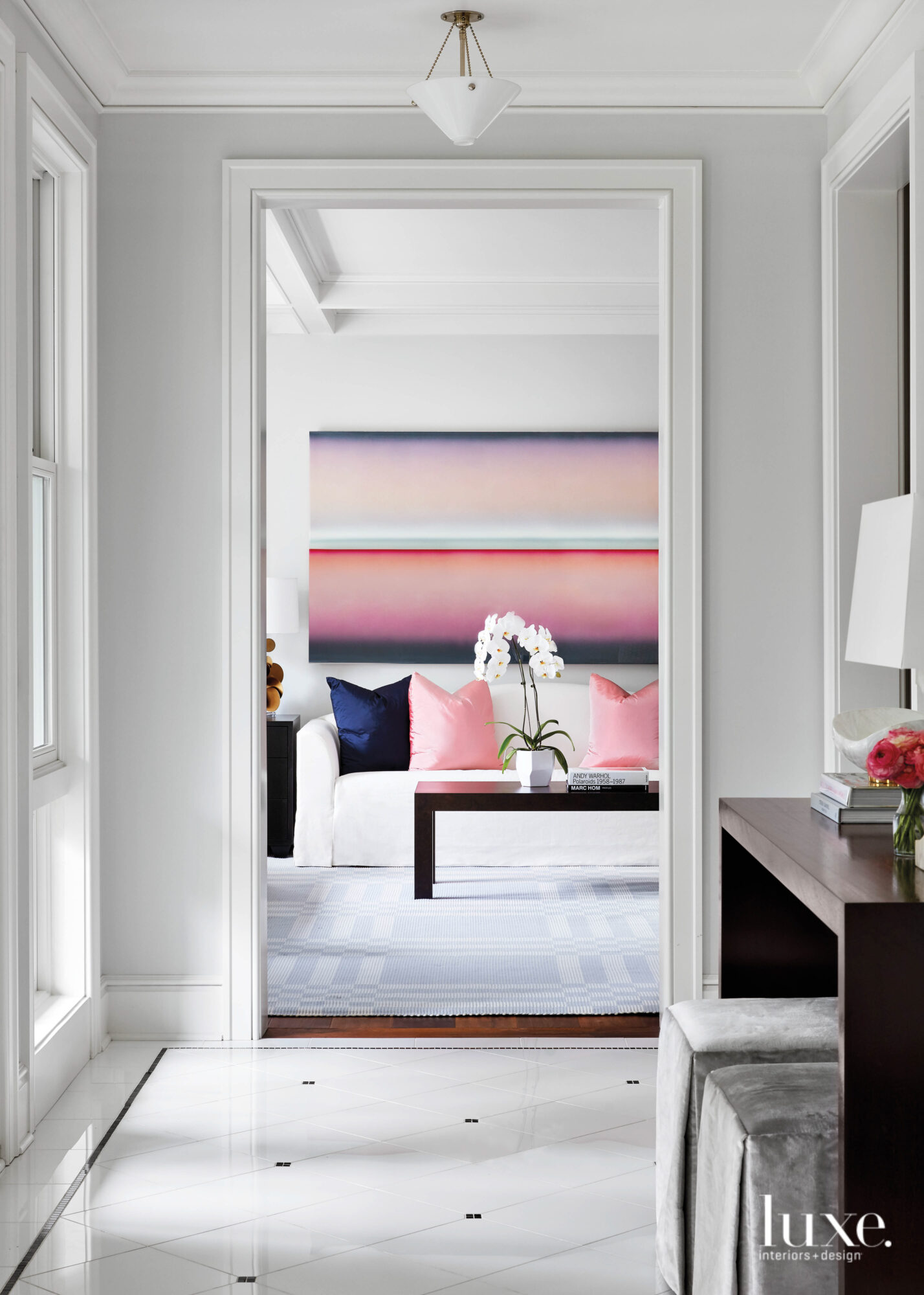 From the foyer you can see Into the living room where a pink-purple-and-blue painting by Casper Brindle hangs above the sofa.