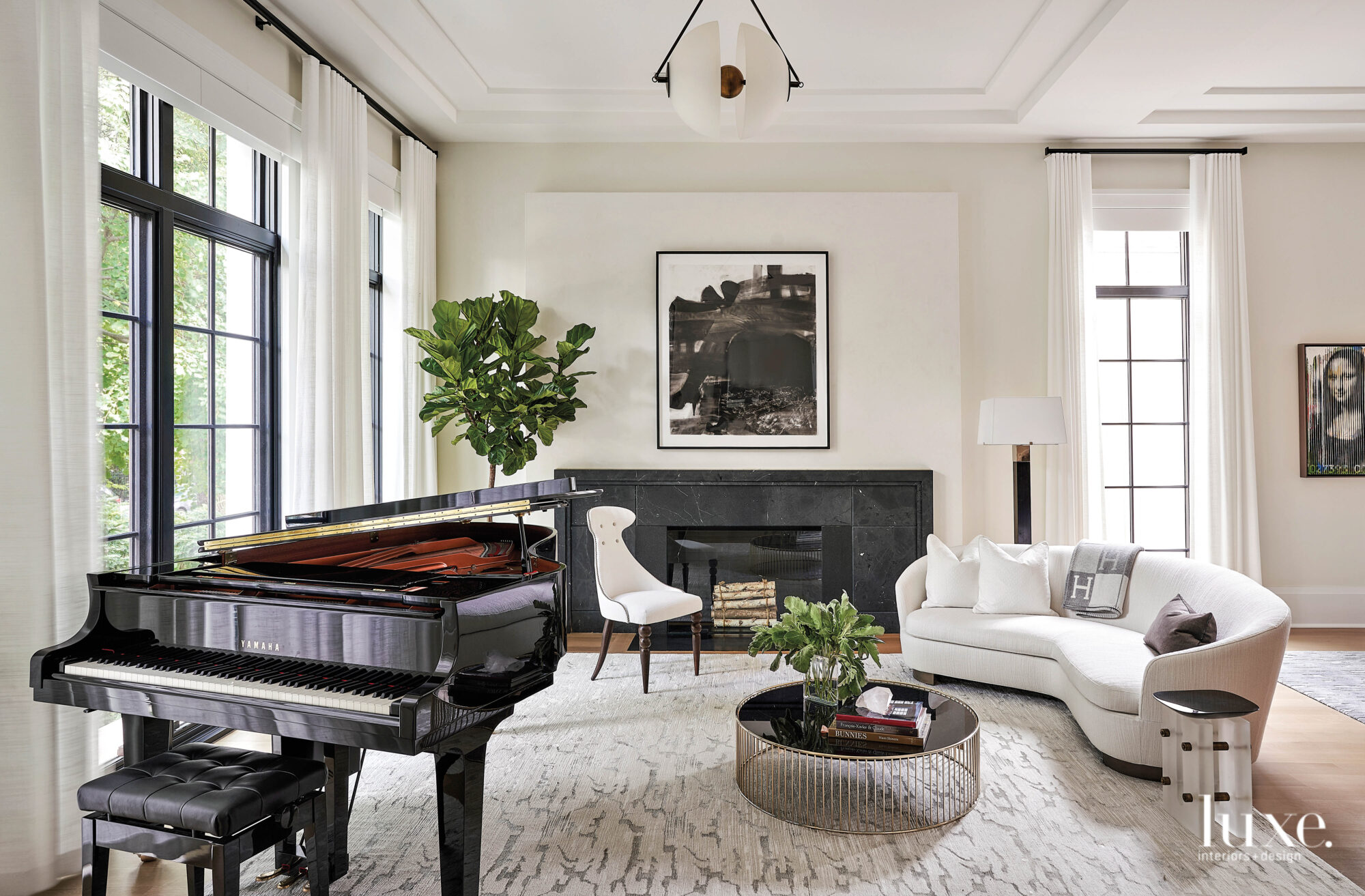 The living room has a a baby grand piano, a white curved sofa and black marble fireplace.
